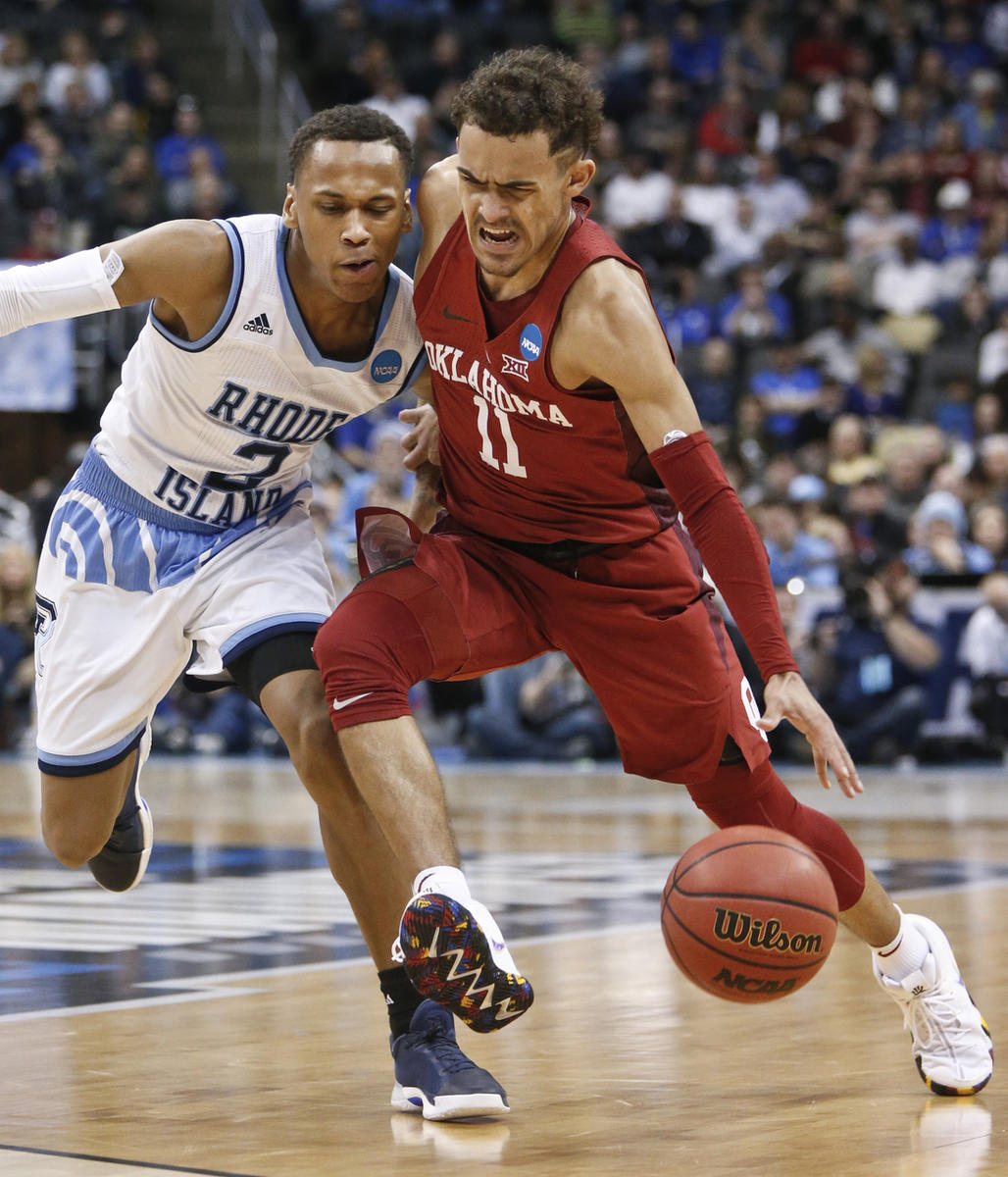 Oklahoma's Trae Young (11) drives as Rhode Island's Fatts Russell (2) defends during the second half of an NCAA men's college basketball tournament first-round game, Thursday, March 15, 2018, in Pittsburgh. Rhode Island won 83-78 in overtime to advance to