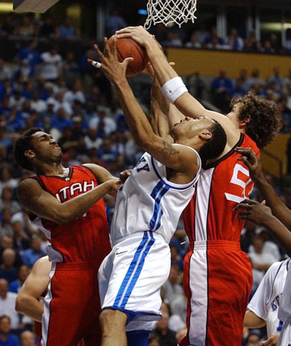 Kentucky guard Gerald Fitch, center, fights for a rebound with Utah's Tim Drisdom, left, and Tim Frost, right, at the NCAA Midwest Regional basketball tournament on Sunday, March 23, 2003, in Nashville, Tenn.