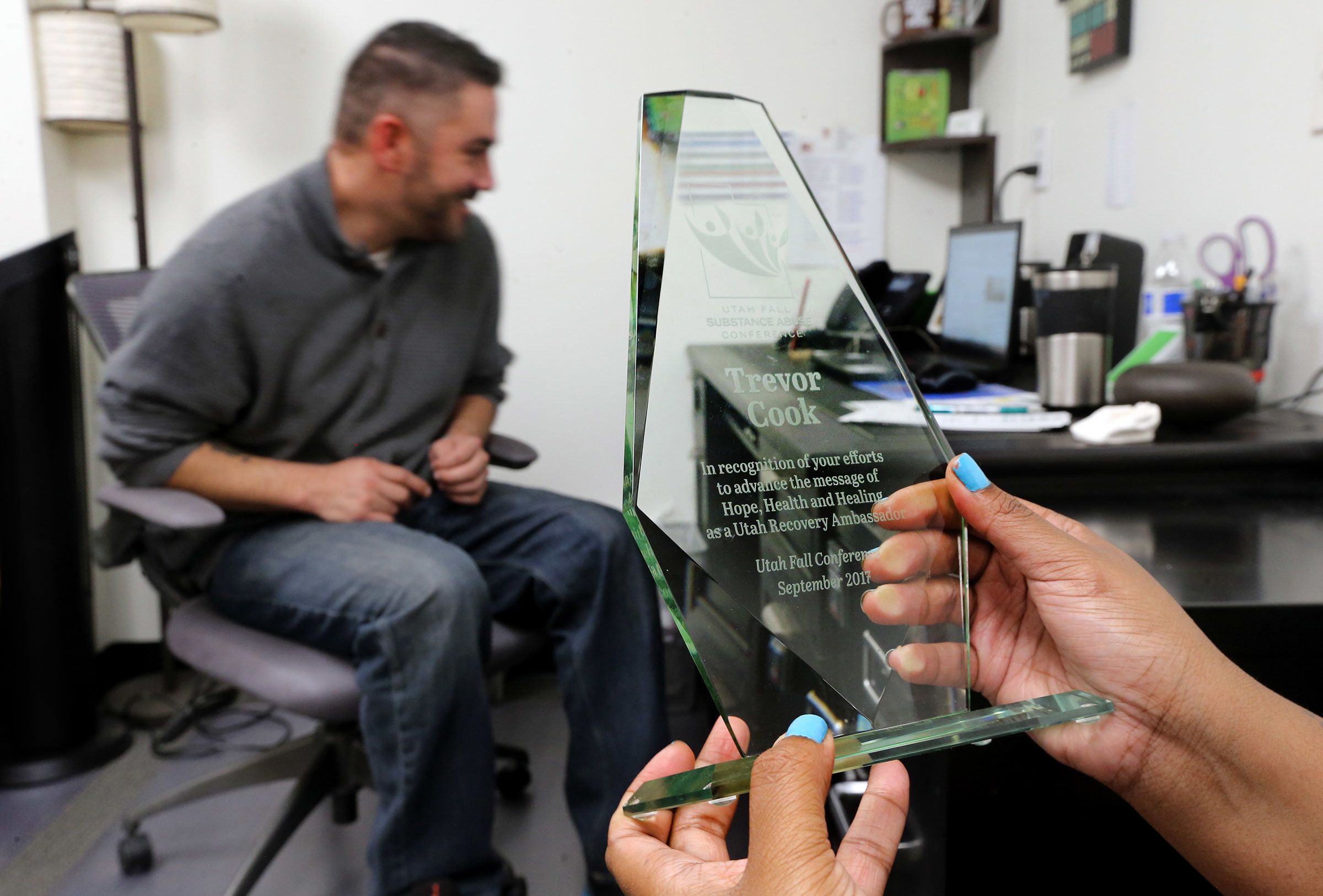 Shantel Cozart holds an award that Trevor Cook, a recovering addict, received as she talks with him at his USARA in his Salt Lake City office on Friday, Dec. 8, 2017.