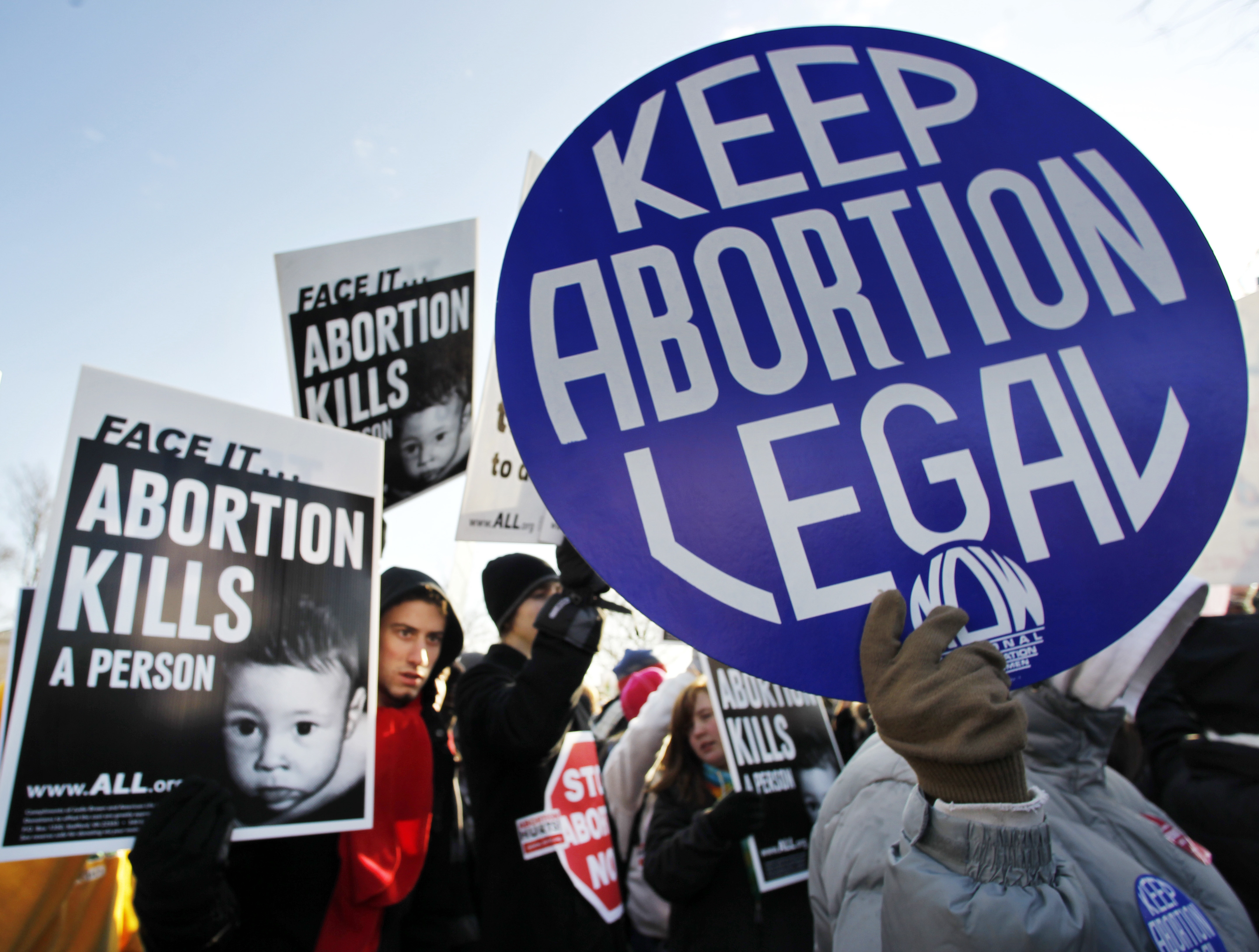Anti-abortion and abortion activists stand side by side in front of the U.S. Supreme Court, in Washington, Monday, Jan. 24, 2011, during a rally against Roe v. Wade on the anniversary of the U.S. Supreme Court decision.