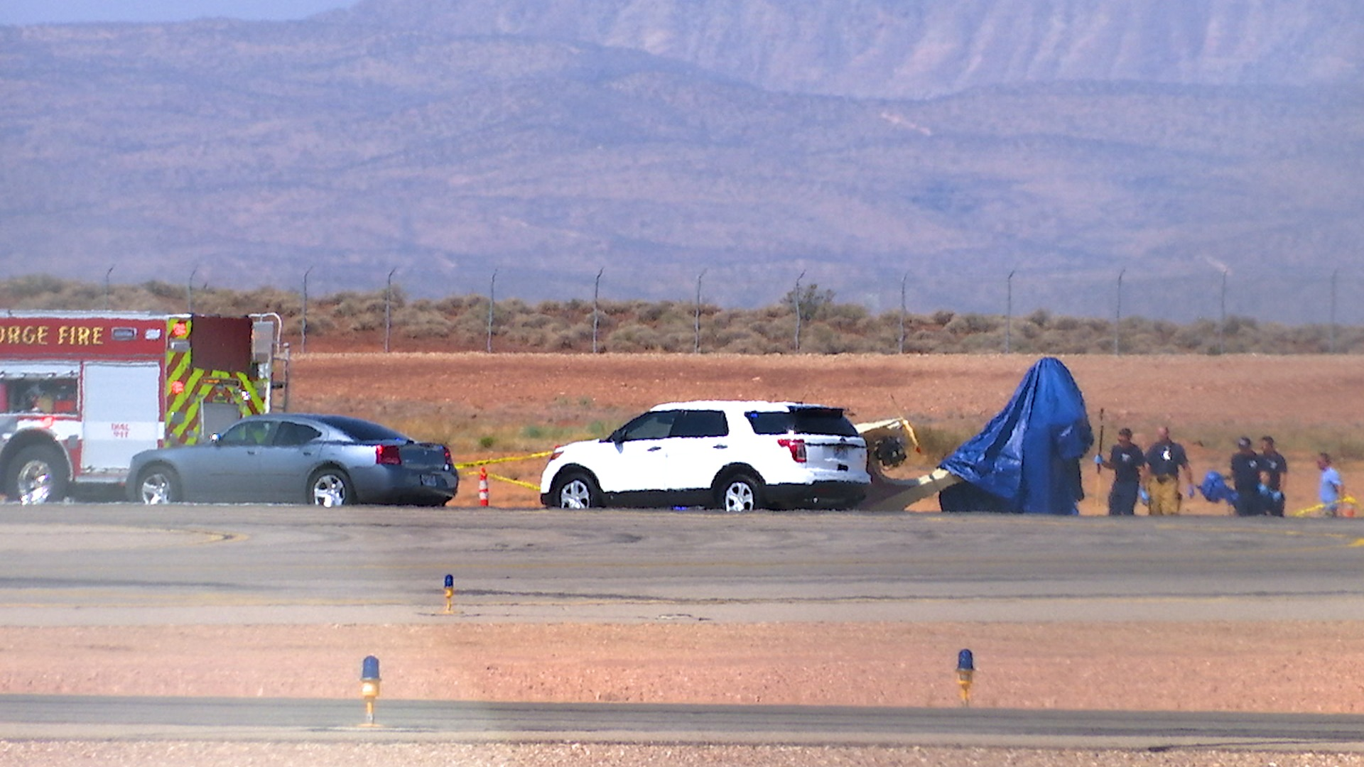 Emergency personnel place a blue tarp on the tail of an aircraft that crashed at St. George Regional Airport, killing the pilot, Sterling Palmer, 69, of St. George, on Saturday, Aug. 11, 2018.