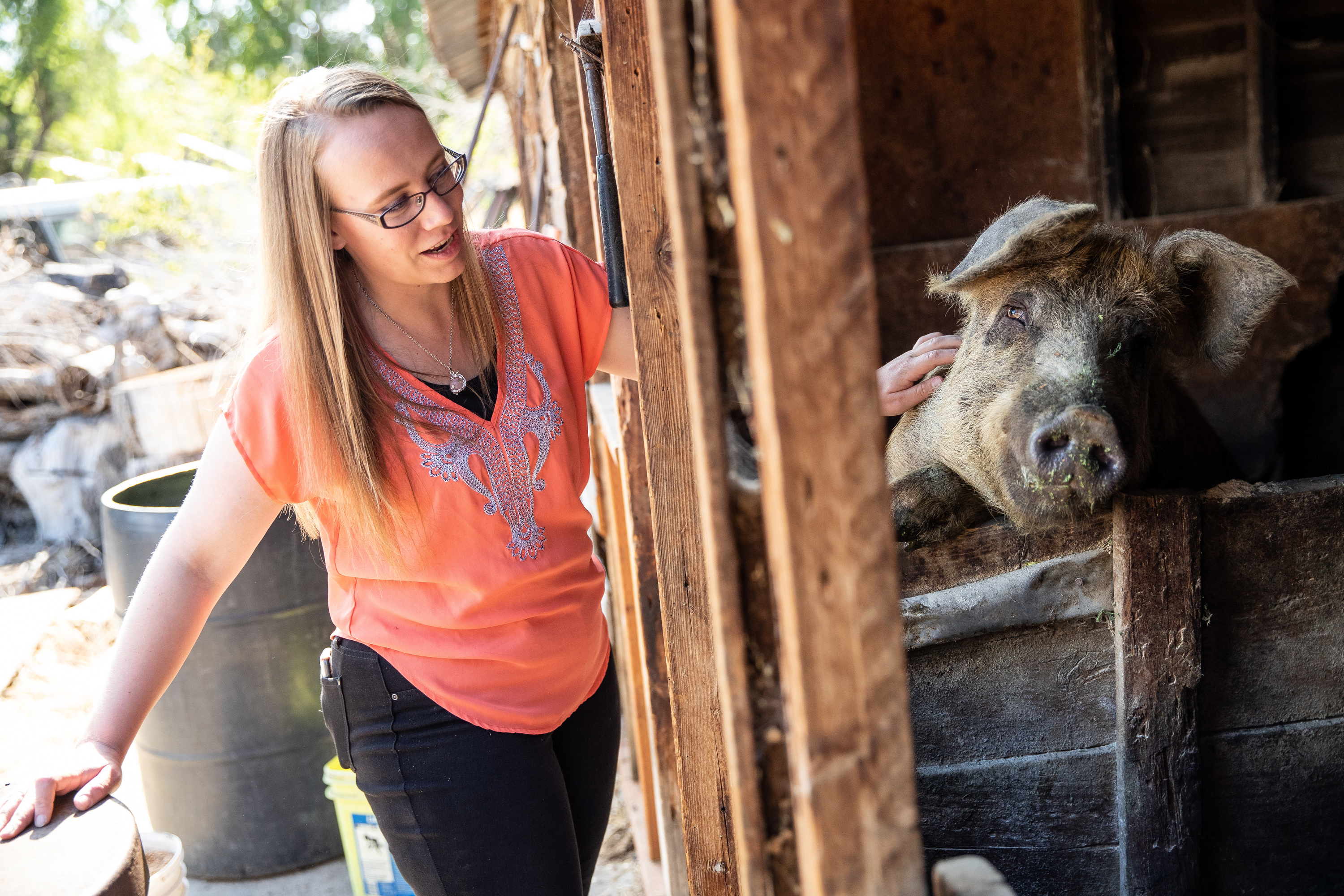 Alexandria, 23, pets Ginger, one of her family's pigs, at her home in Herriman on Tuesday, May 29, 2018. Alexandria says she likes being around the pigs because they listen without judgement. She also likes working with animals because it gives her a sens