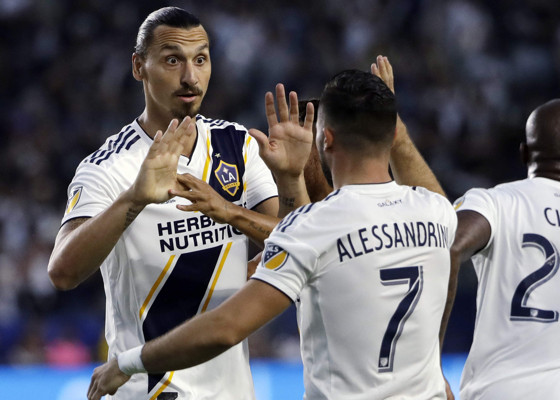 LA Galaxy midfielder Romain Alessandrini (7) celebrates his goal with teammate Zlatan Ibrahimovic during the first half of an MLS soccer match against Minnesota United, Saturday, Aug. 11, 2018, in Carson, Calif.