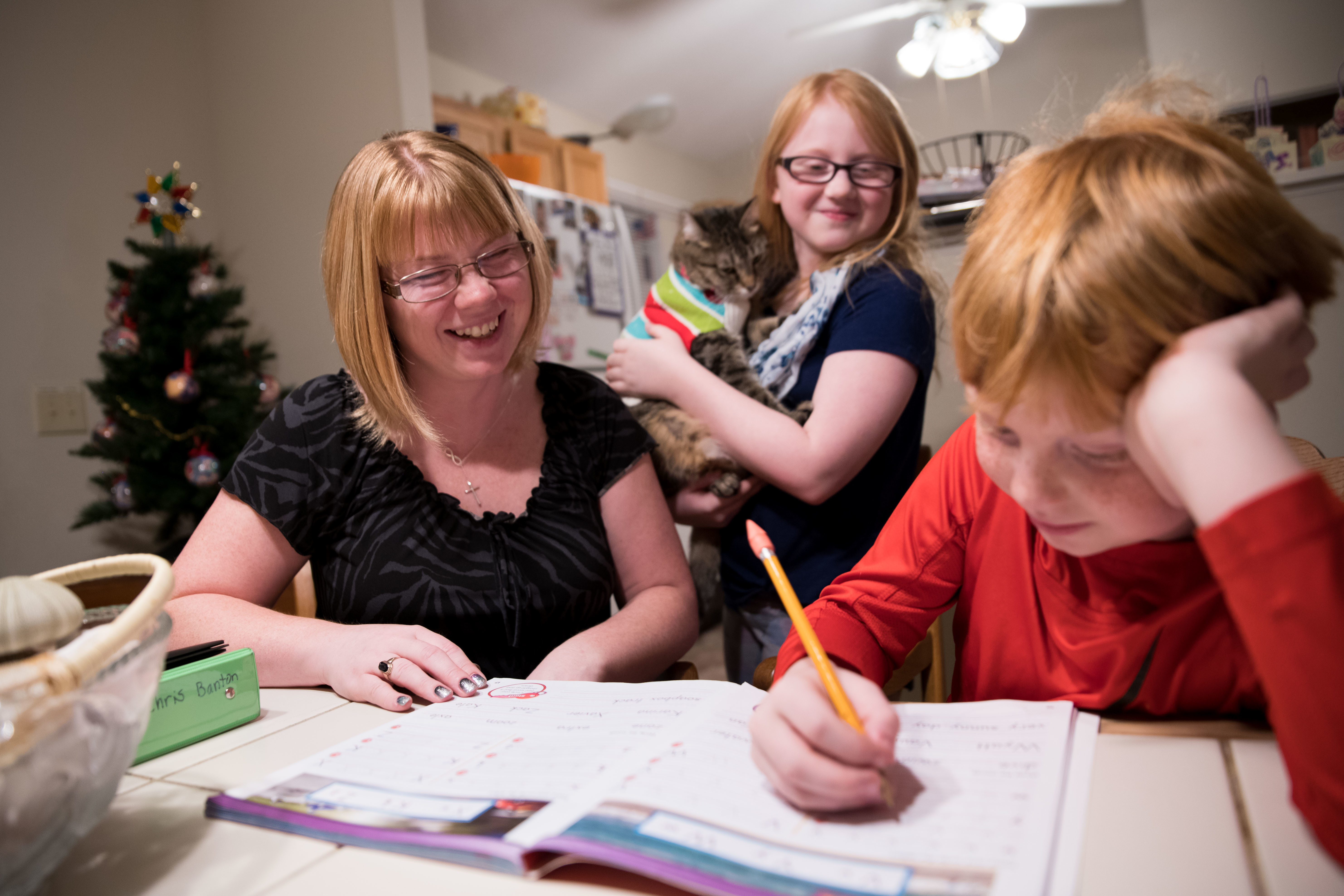 Veronica Banton helps her son, Chris, with homework as her daughter Sara looks on in their home Thursday, Nov. 15, 2018 in Lexington, S.C.