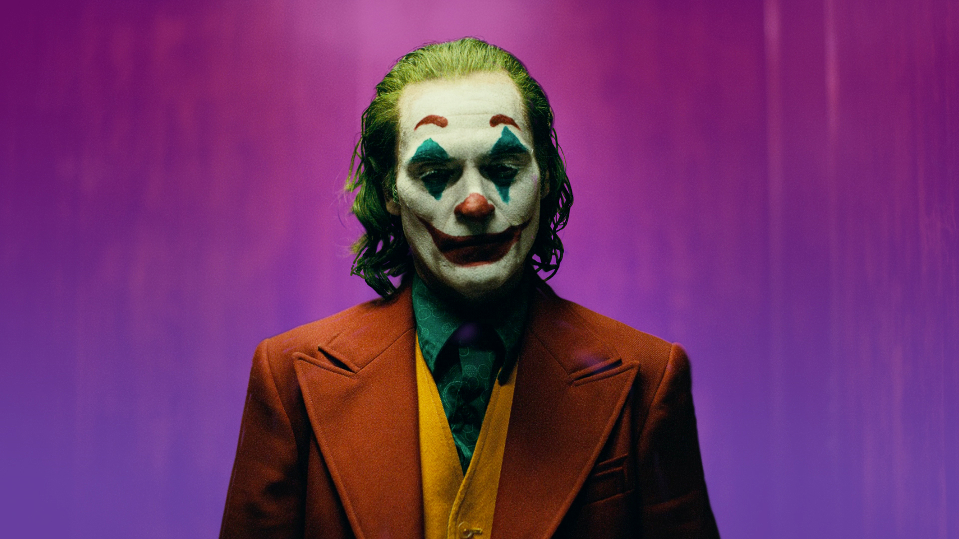 Joker, a man in clown makeup and a red suit with a green shirt and orange vest