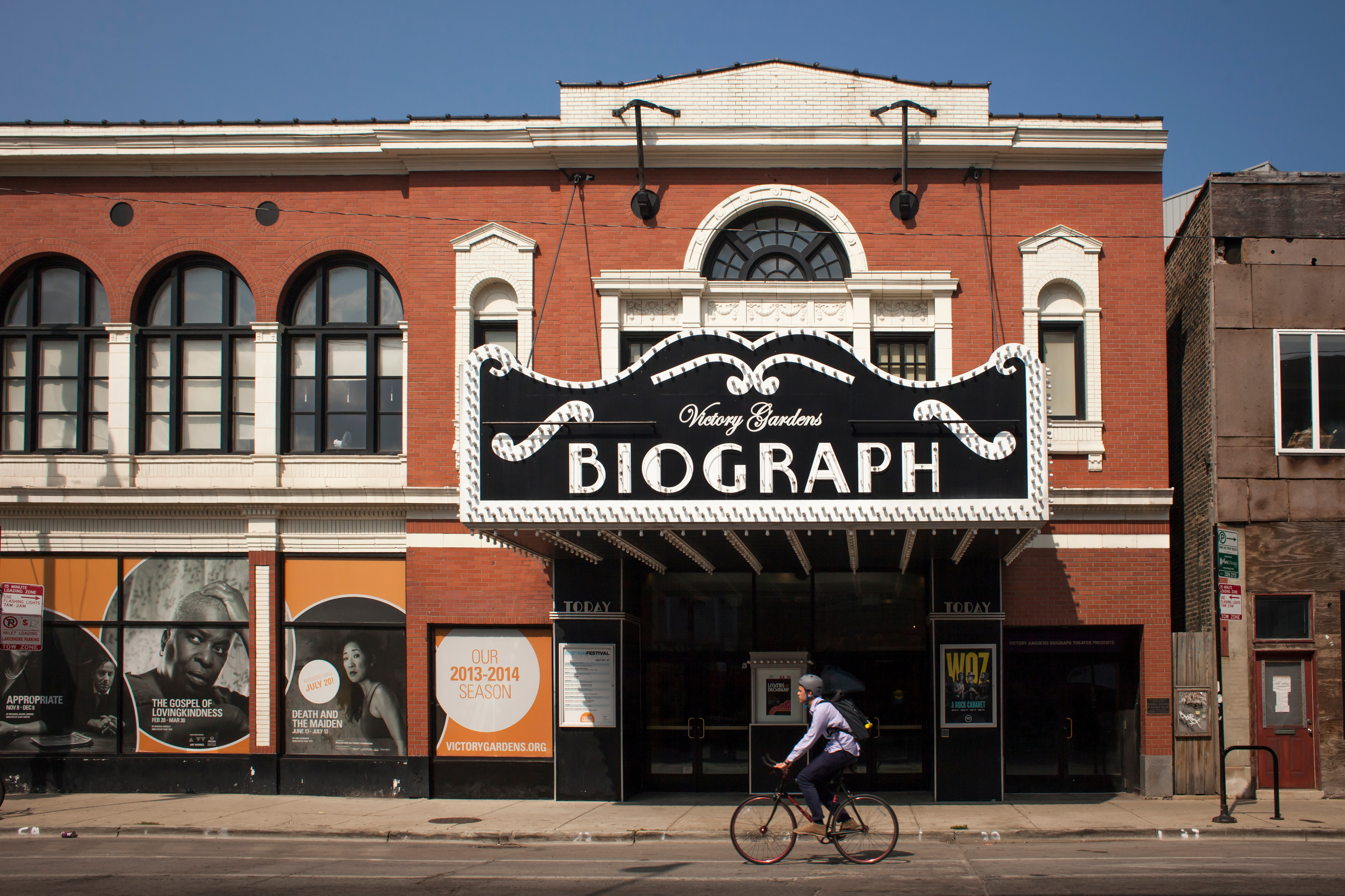 The exterior of a theater in Chicago. The building is red and there is black and white sign that reads: Victory Gardens Biograph.