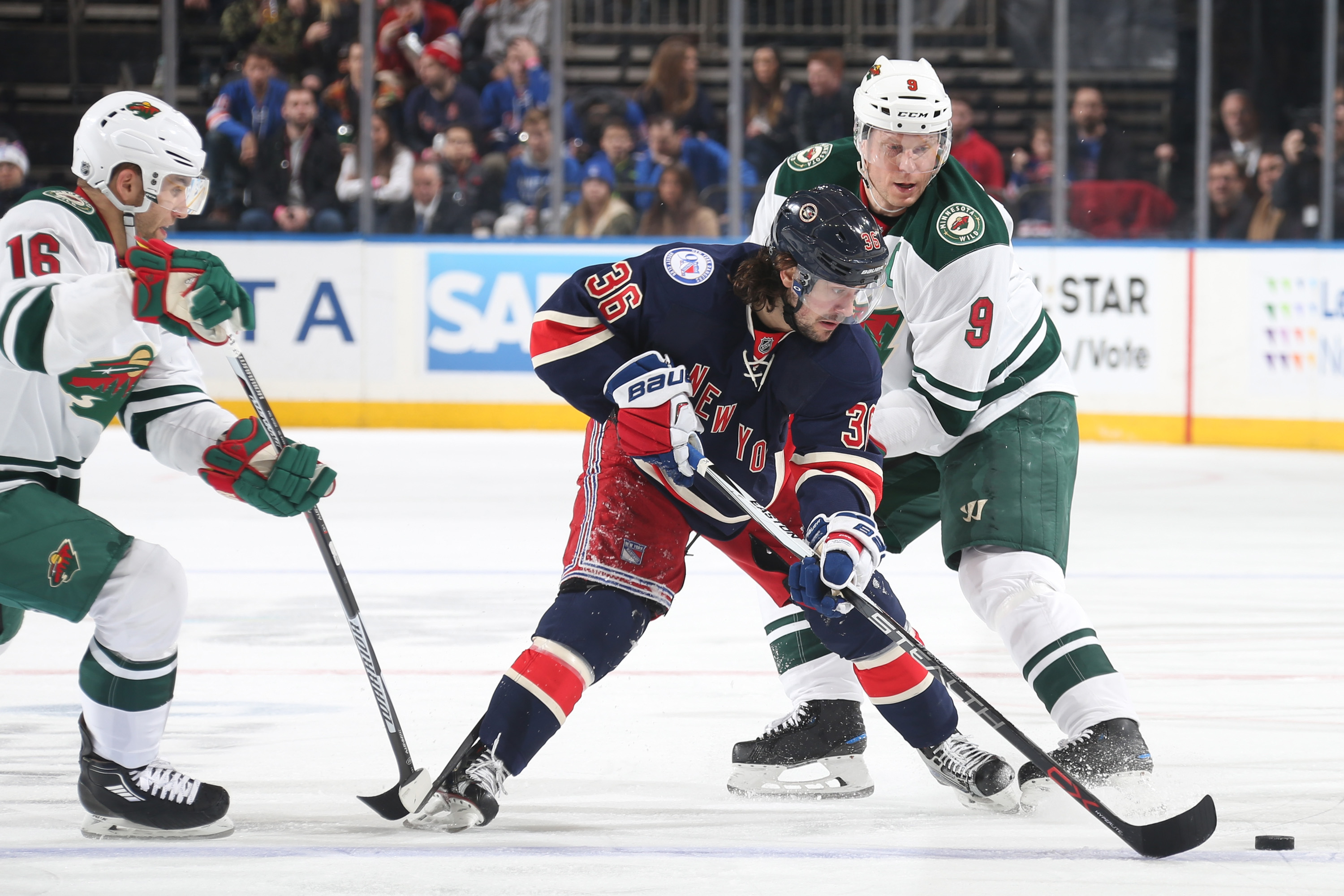 Mats Zuccarello of the New York Rangers skates with the puck against Mikko Koivu and Jason Zucker of the Minnesota Wild at Madison Square Garden on December 23, 2016 in New York City. The Minnesota Wild won 7-4.