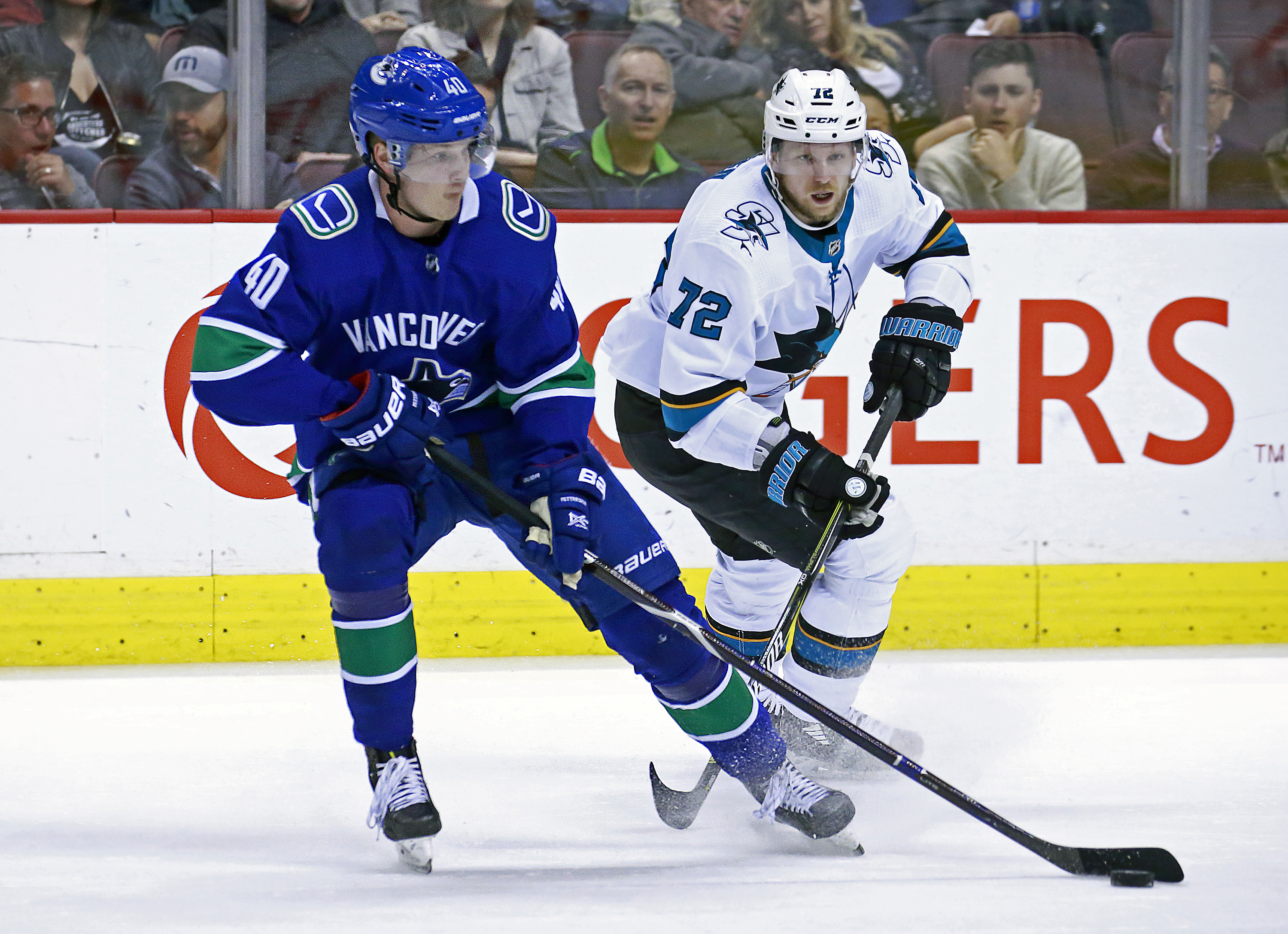 VANCOUVER, BC - APRIL 2: Tim Heed #72 of the San Jose Sharks checks Elias Pettersson #40 of the Vancouver Canucks during their NHL game at Rogers Arena April 2, 2019 in Vancouver, British Columbia, Canada. Vancouver won 4-2.
