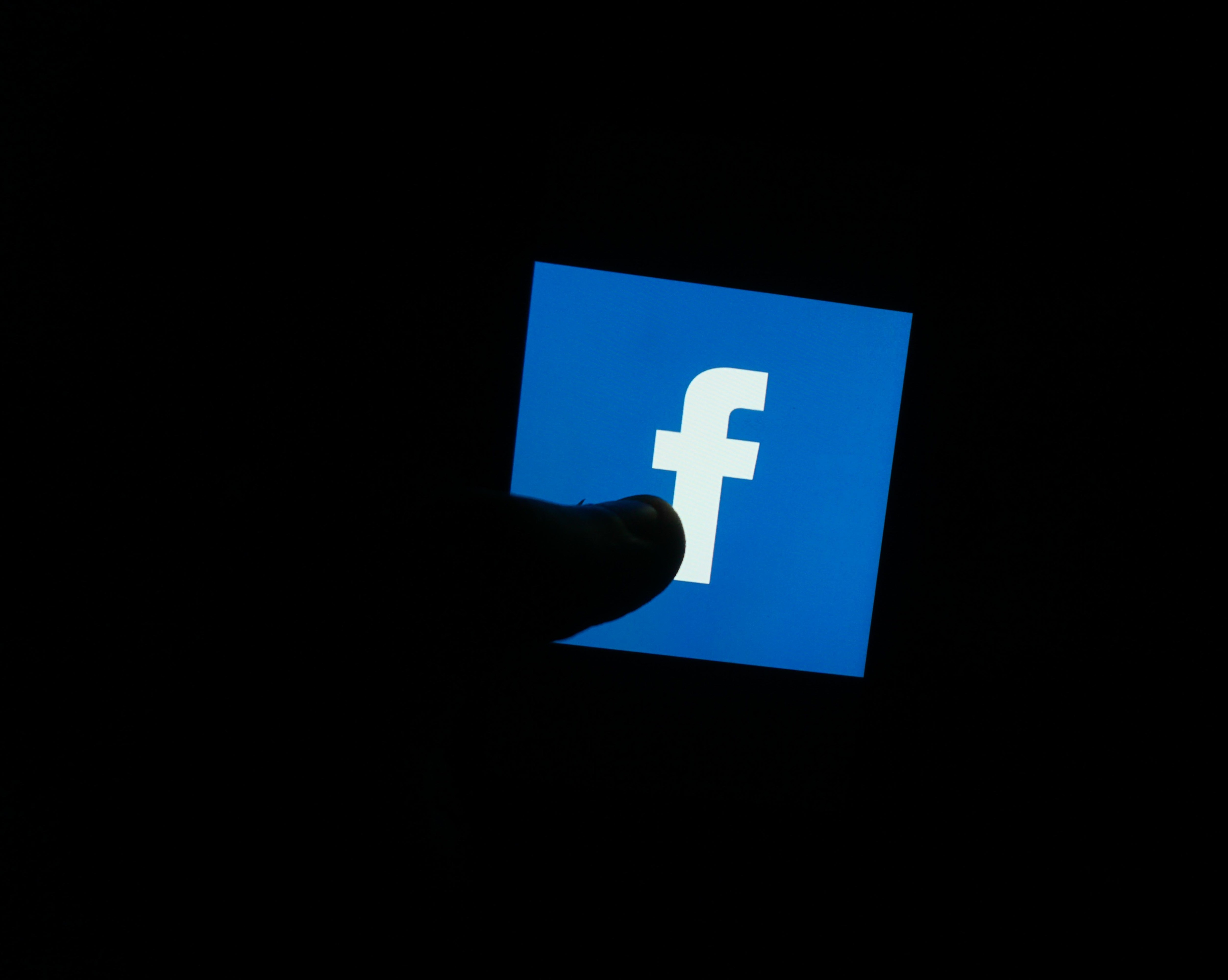 In this photo illustration a Facebook logo is seen displayed on a phone screen with a silhouetted thumb in front of it.