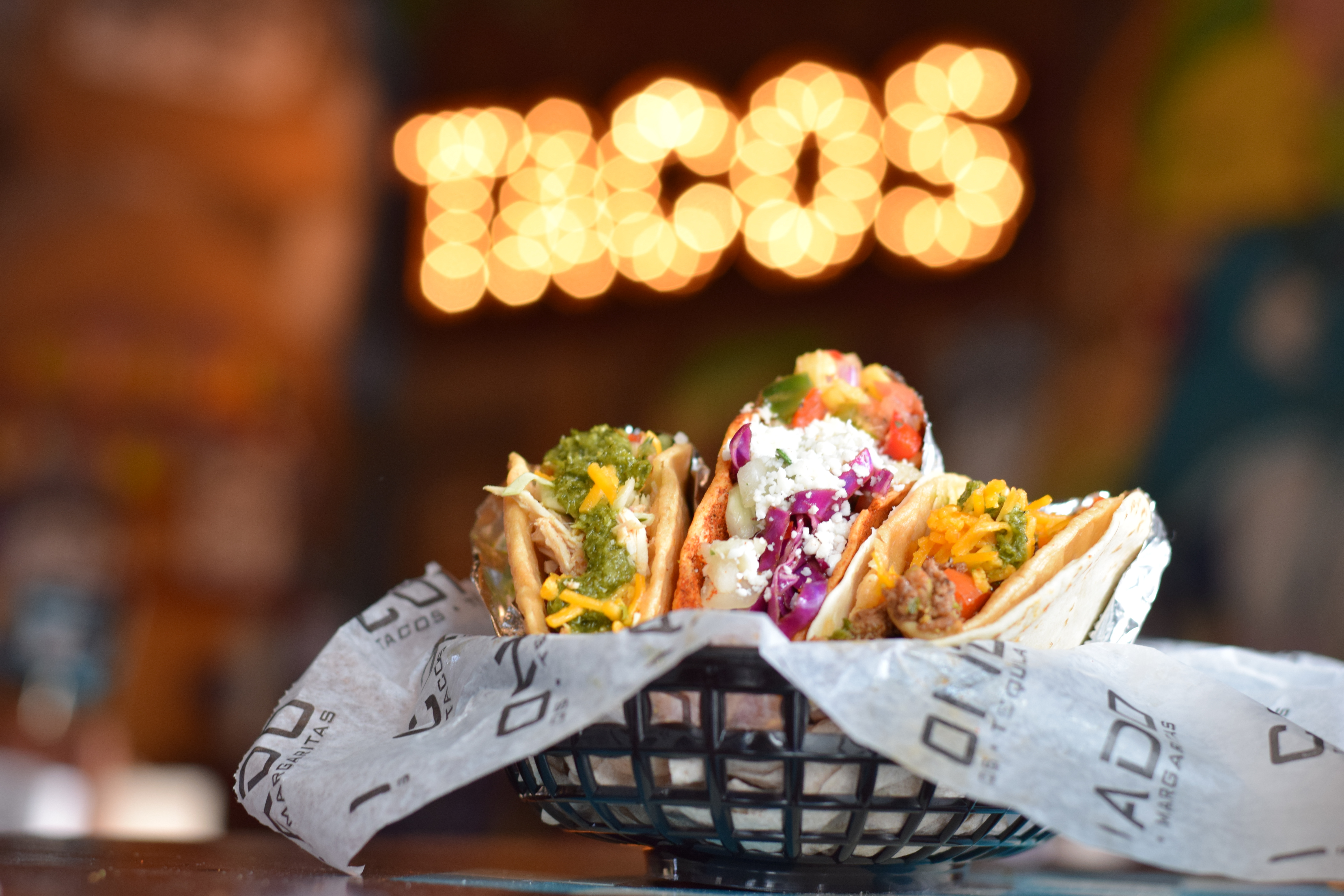 """Three tacos in a black plastic basket lined with paper and a lighted up sign reading """"Tacos"""" in the background."""