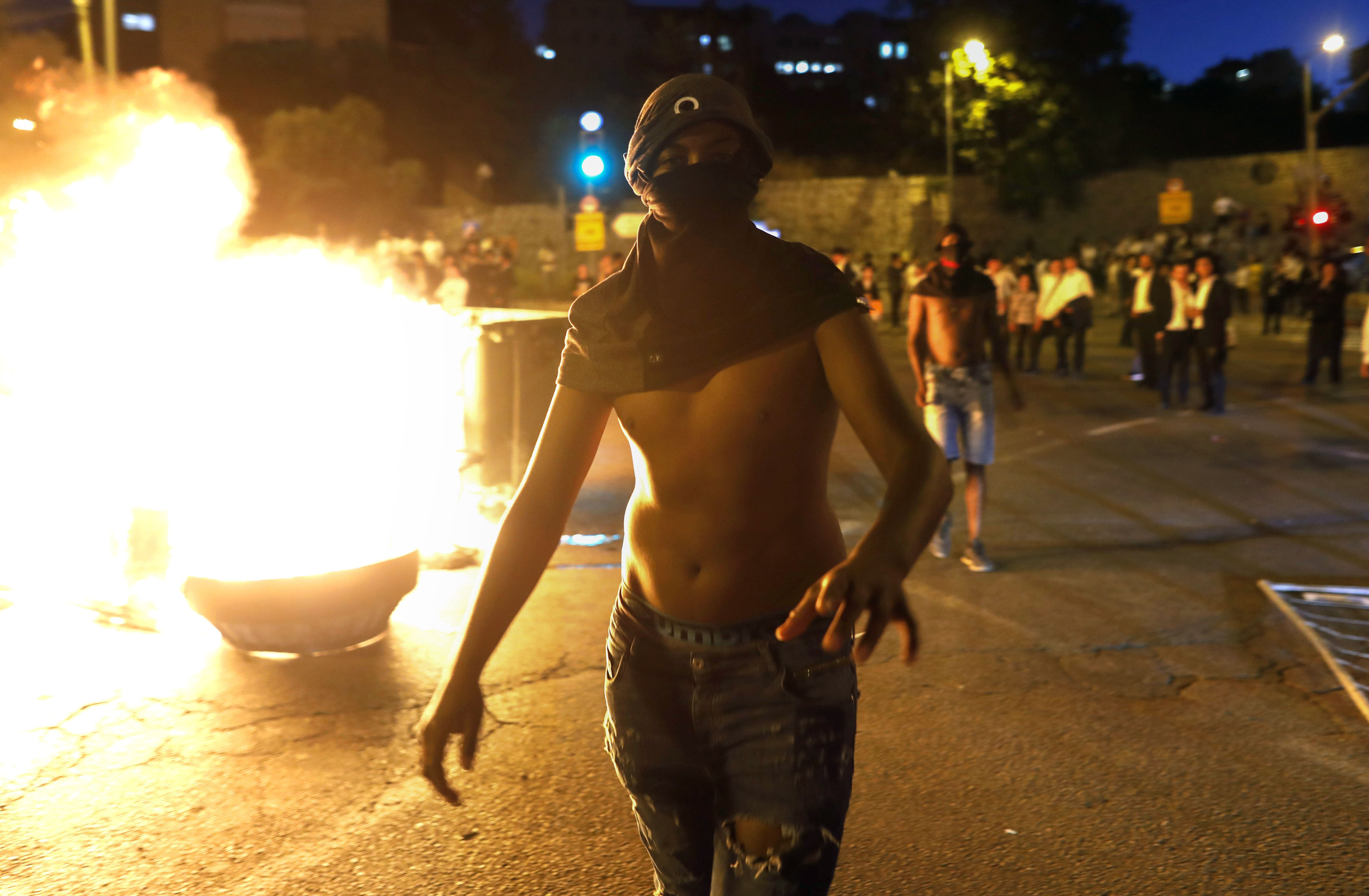 A masked Israeli member of the Ethiopian community walks past a burning barrier blocking the main entrance to Jerusalem on July 02, 2019, to protest the killing of Solomon Tekah, a young man of Ethiopian origin who was killed by an off-duty police officer