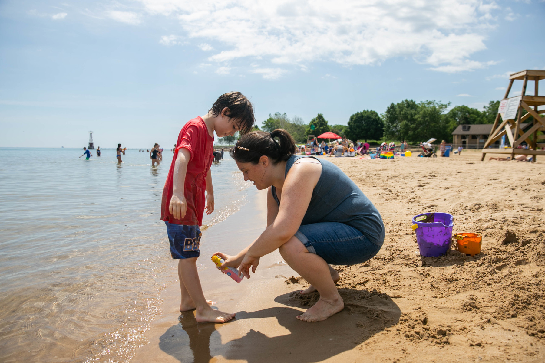 Jamie Prahl, 37, puts sunscreen on her son Wesley at Foster Beach.