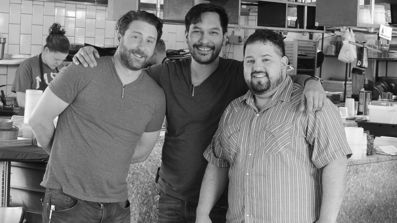 The three chefs embrace and smile to the camera