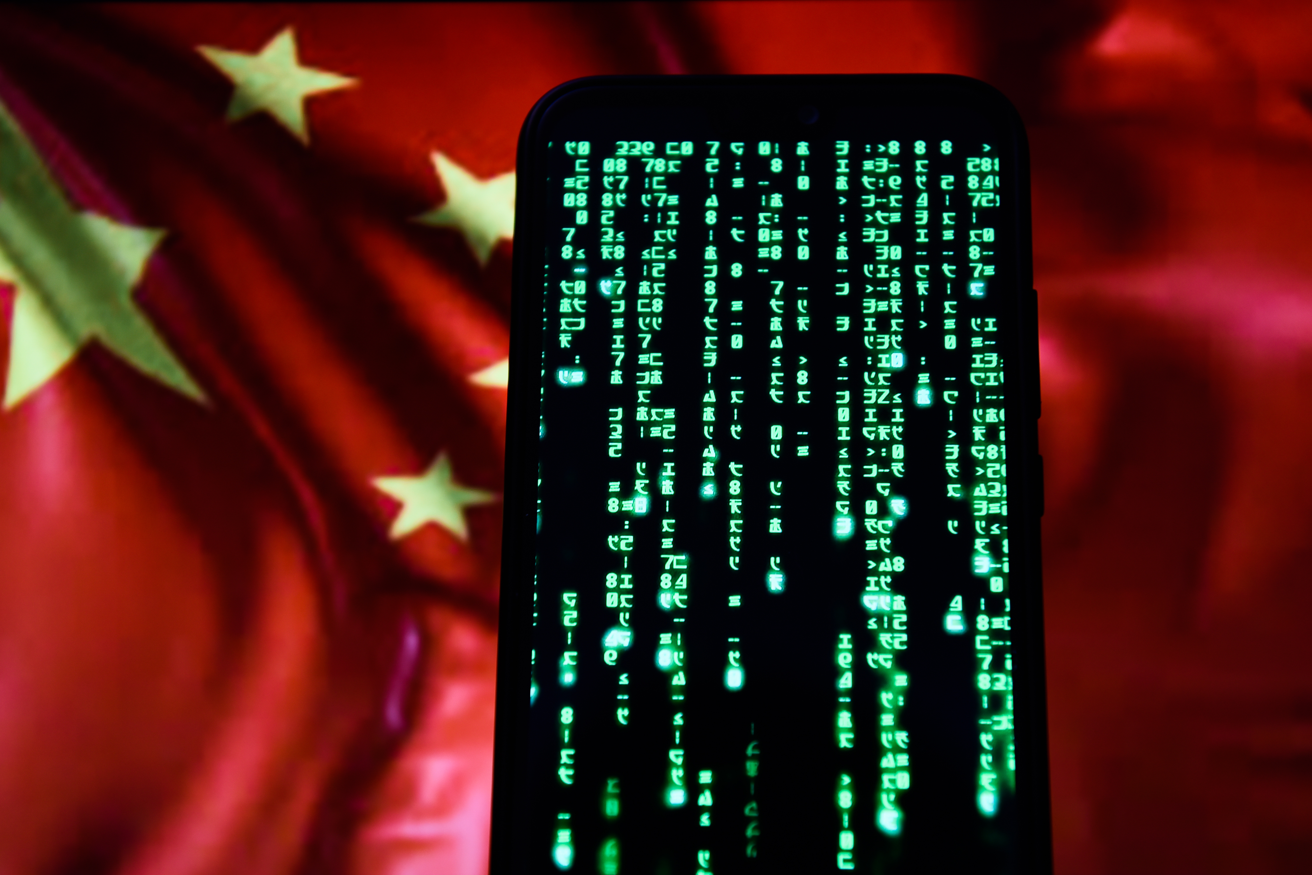A photo illustration of fictional code from The Matrix on an Android phone with Chinese flag in the background.