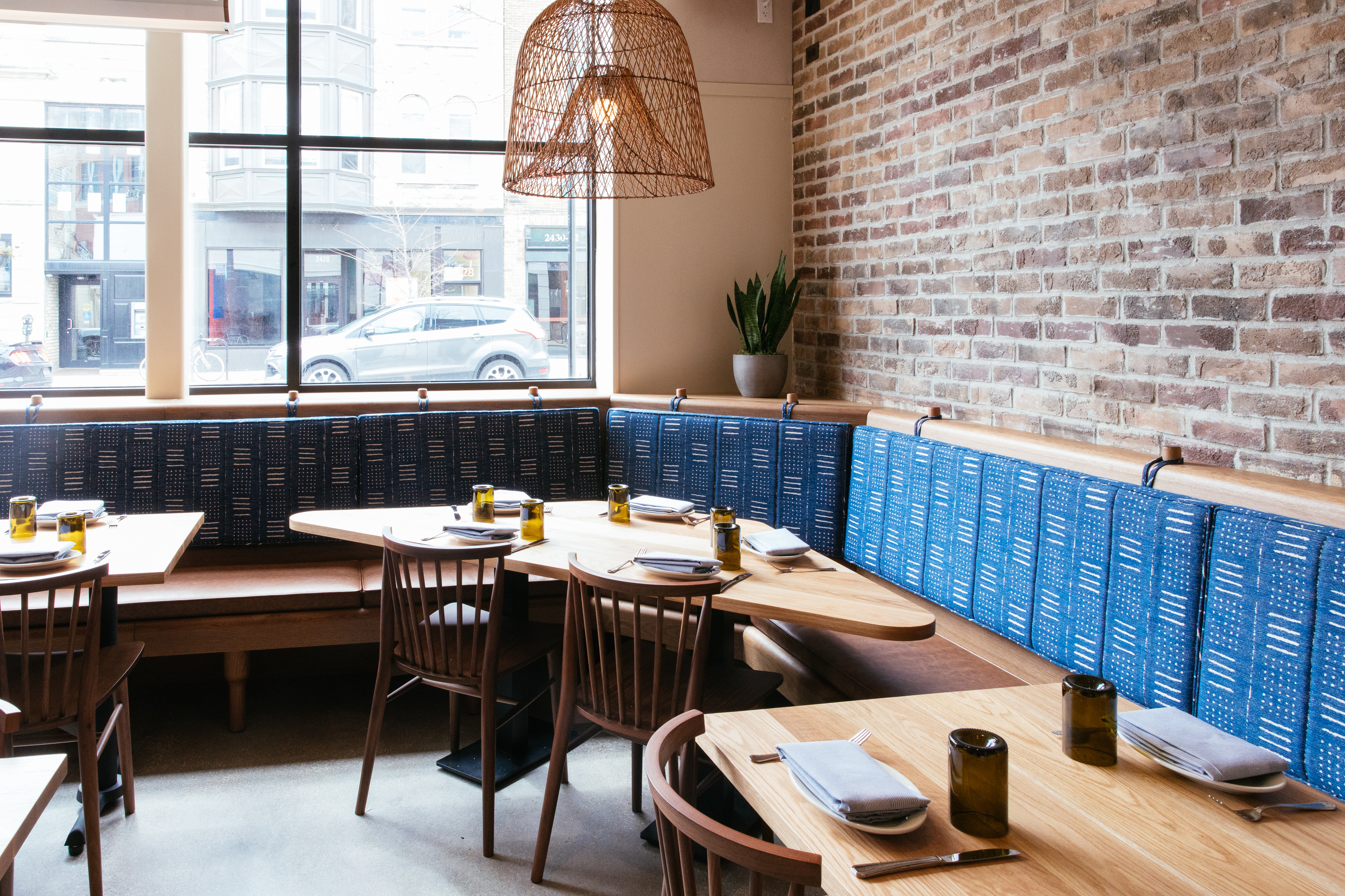 A dining room with a long wooden banquette