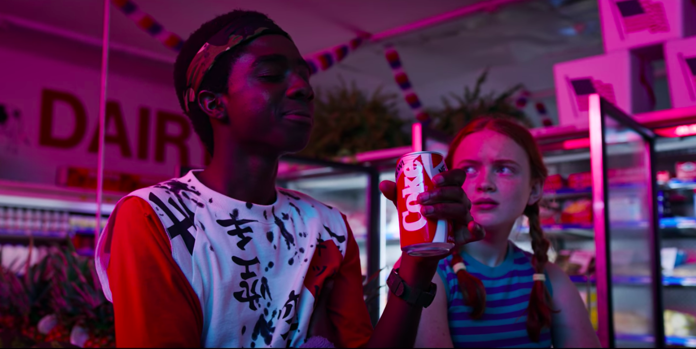 A young man drinks a can of New Coke while a young woman gives him a Look in the background.