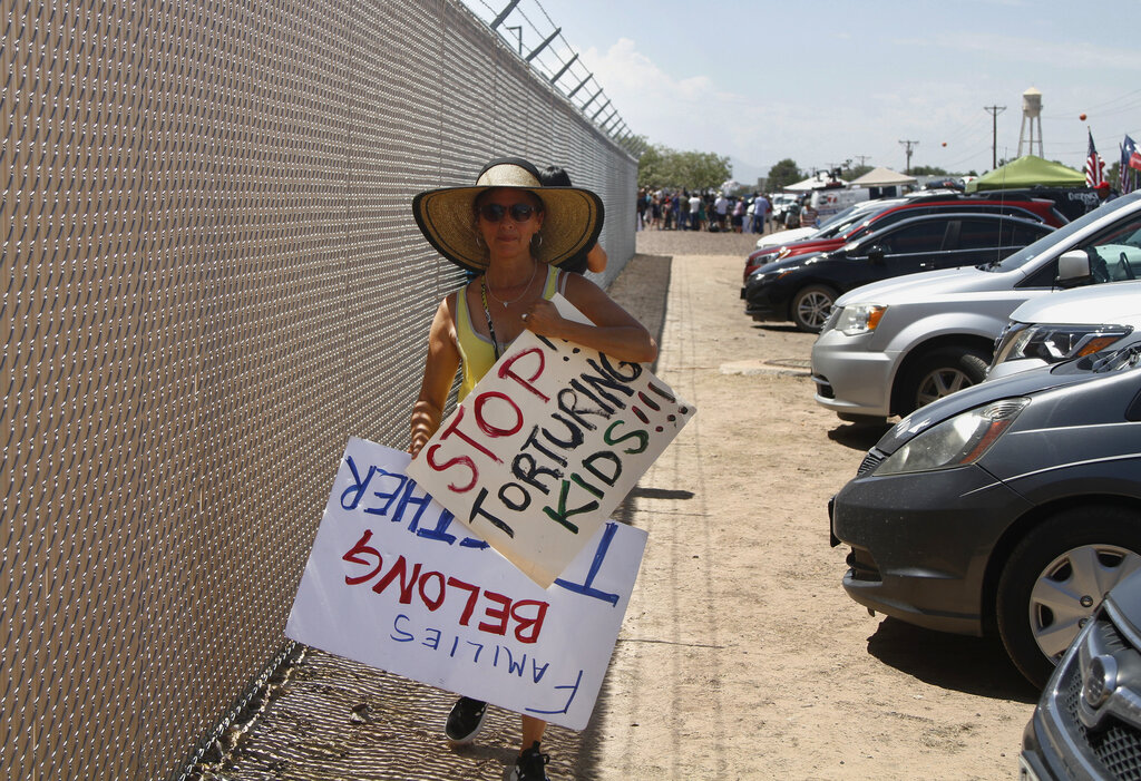 Woman protesting with signs by holding center in Clint, Texas
