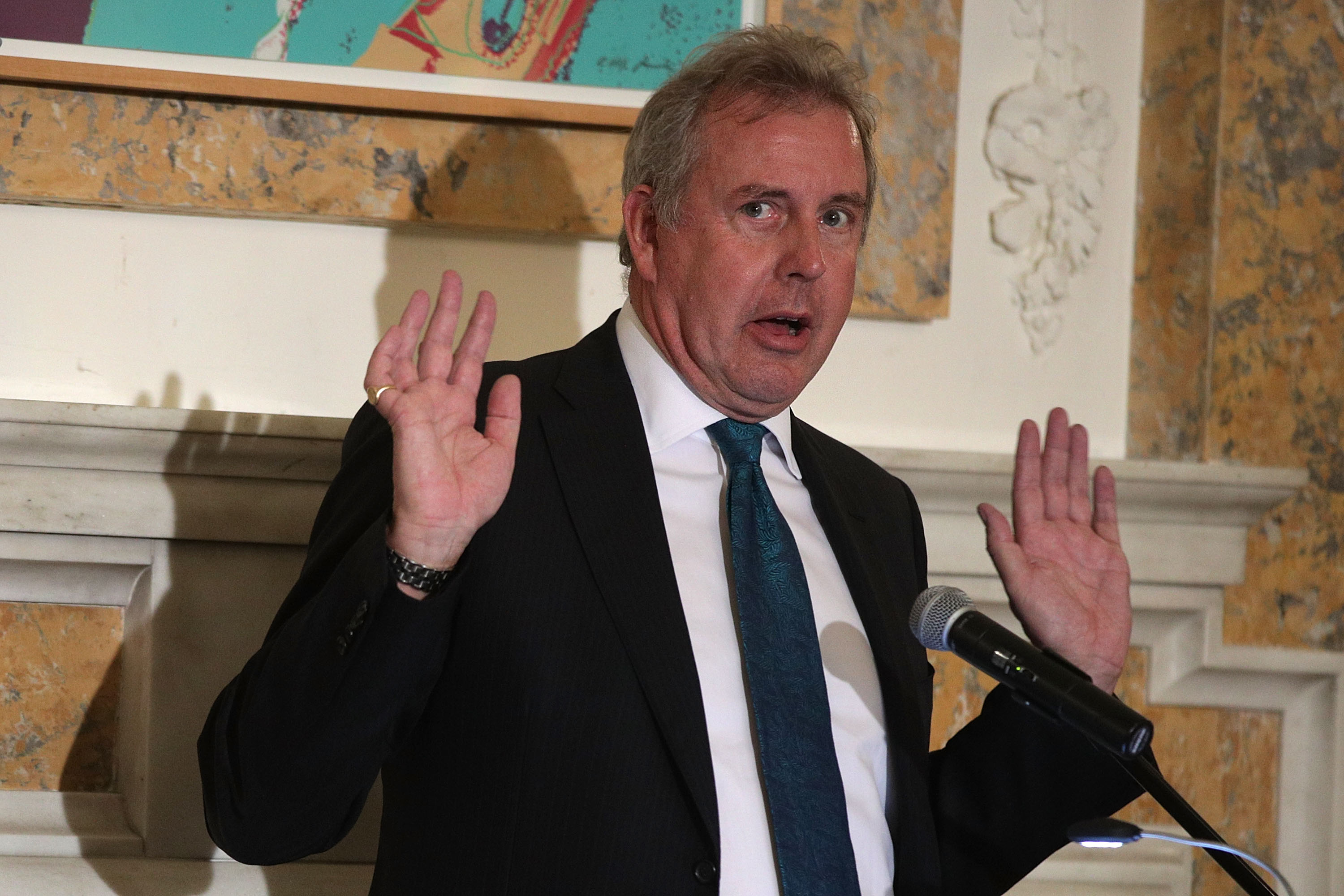 UK Ambassador to the UK Kim Darroch standing in front of a microphone and holding up his hands.