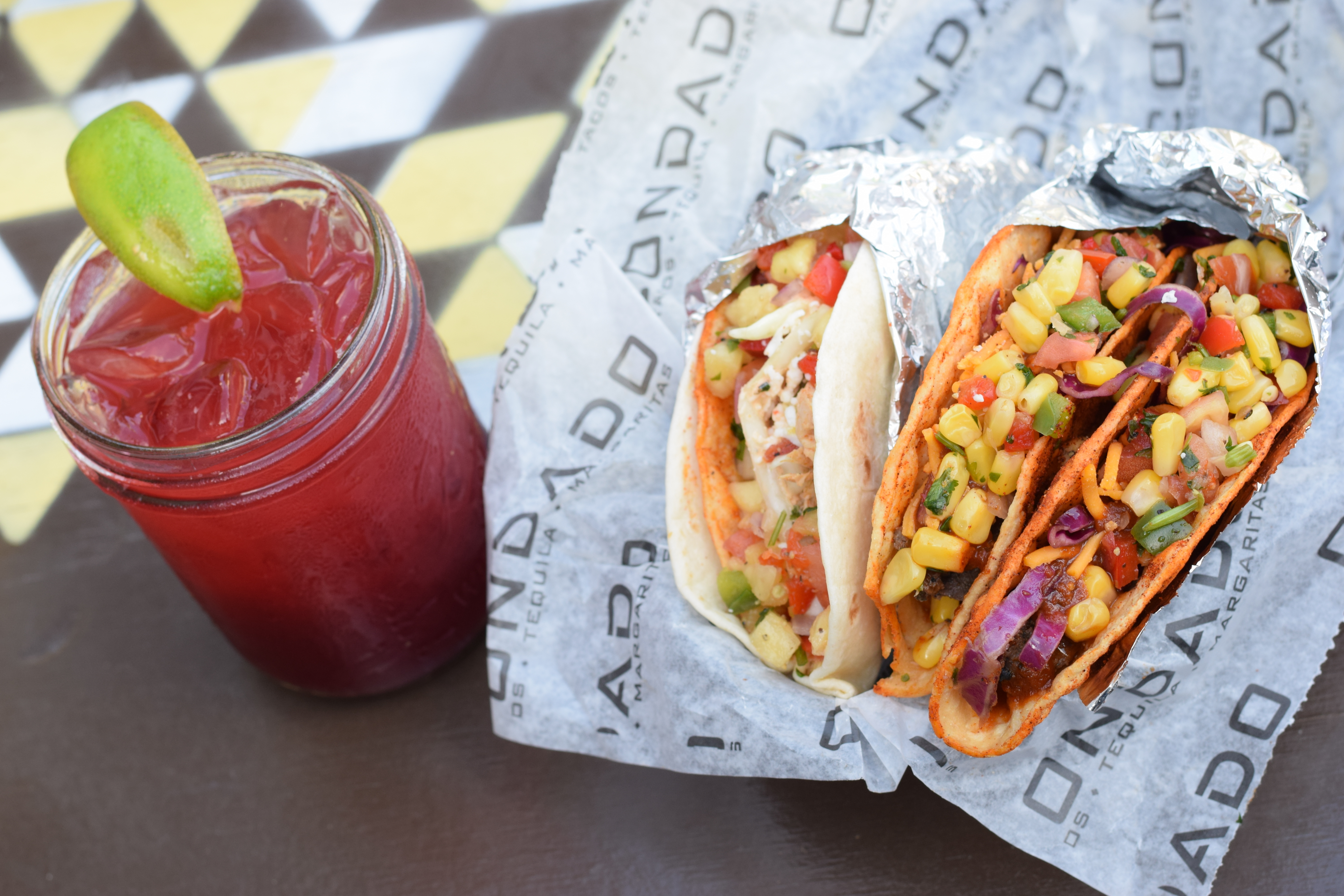 A red colored margarita with a lime in a mason jar, on soft shell flour taco and two hard shell tacos.