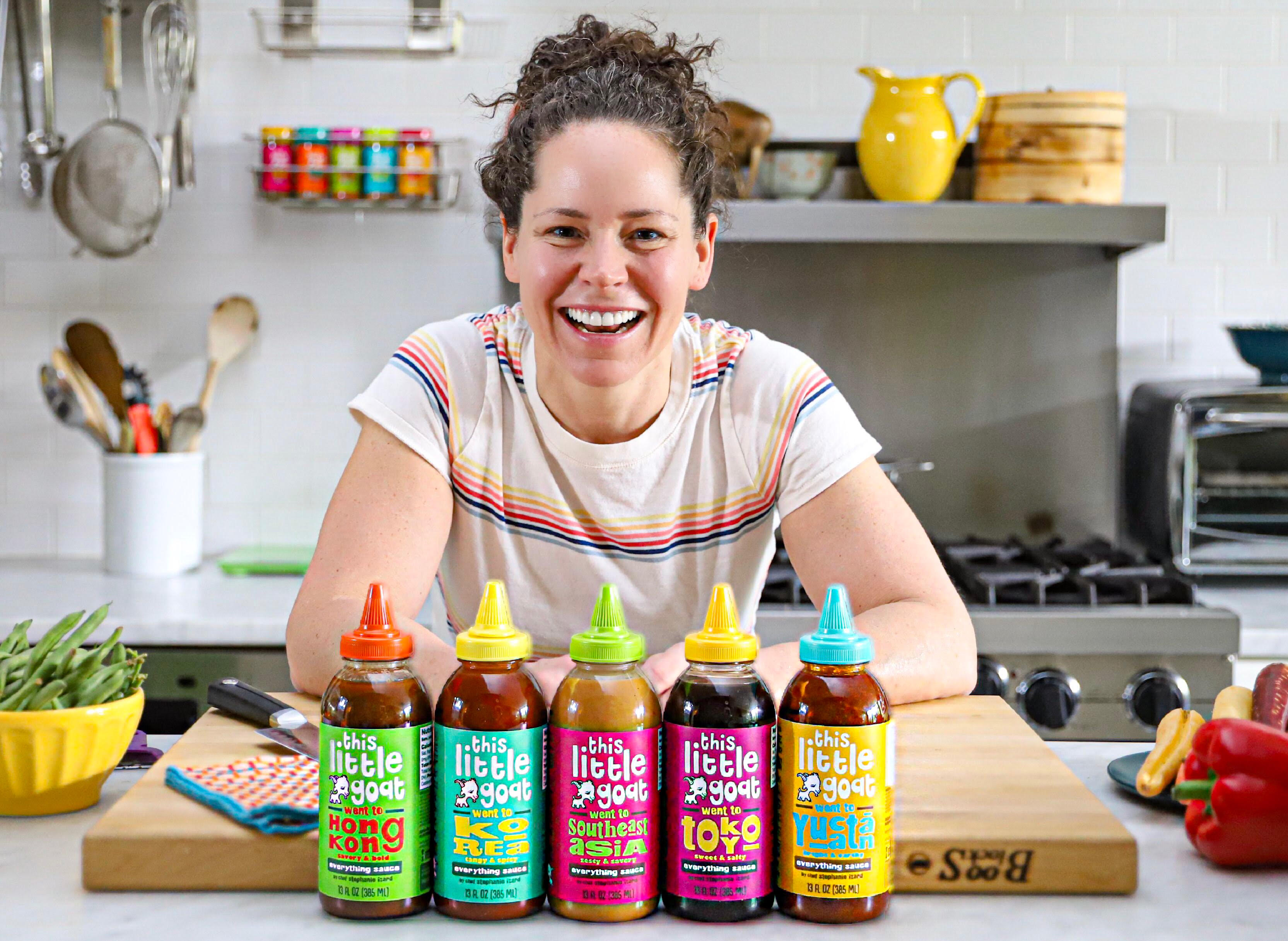Stephanie Izard, a white woman with curly dark hair, smiles widely and leans on a cutting board behind a row of bottled sauces.
