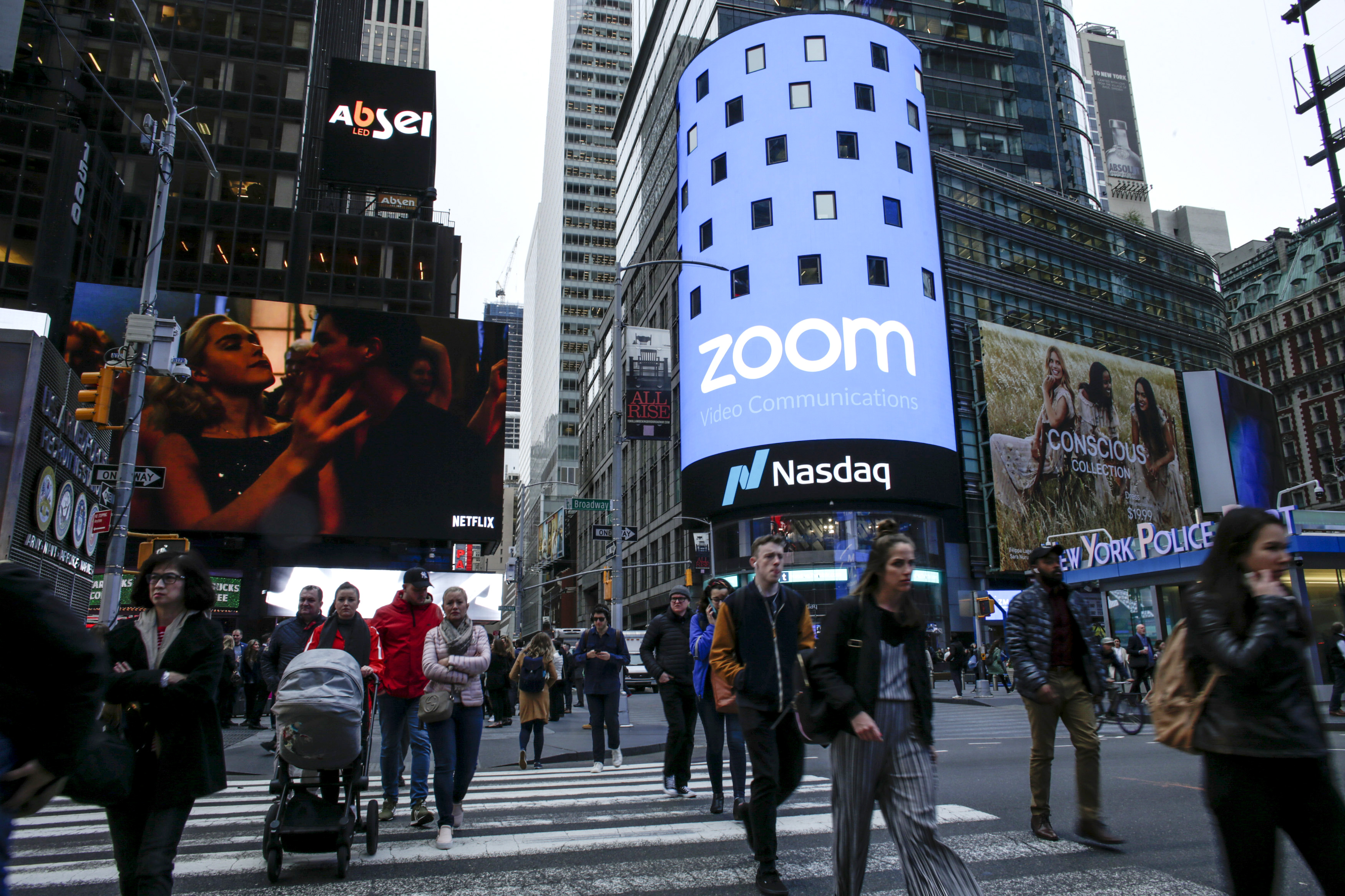People on the street in New York City in front of an ad for video-conferencing software Zoom on the day it went public on the Nasdaq stock exchange.