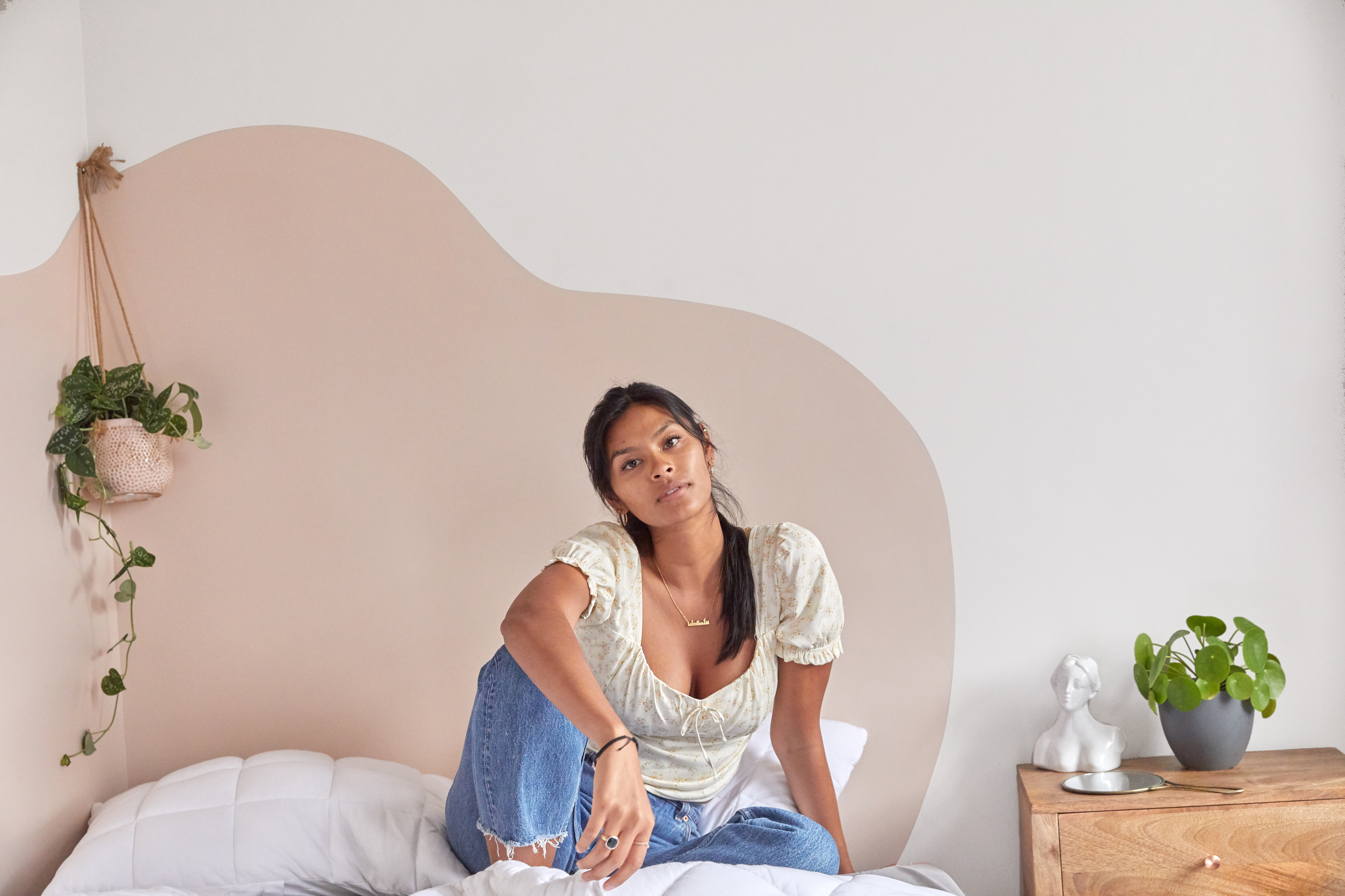 Girl sitting on bed in front of white and pink wall