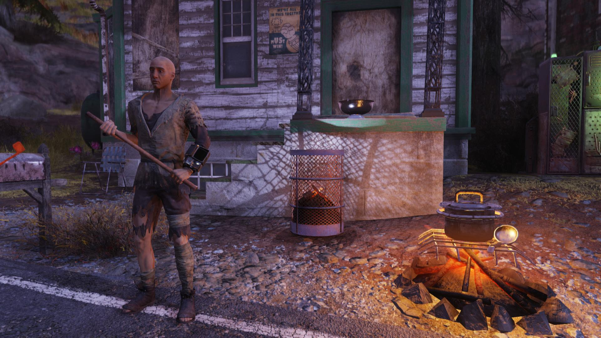 a man dressed in tattered clothes holds a stick while standing by a campfire in front of a roadside house in Fallout 76