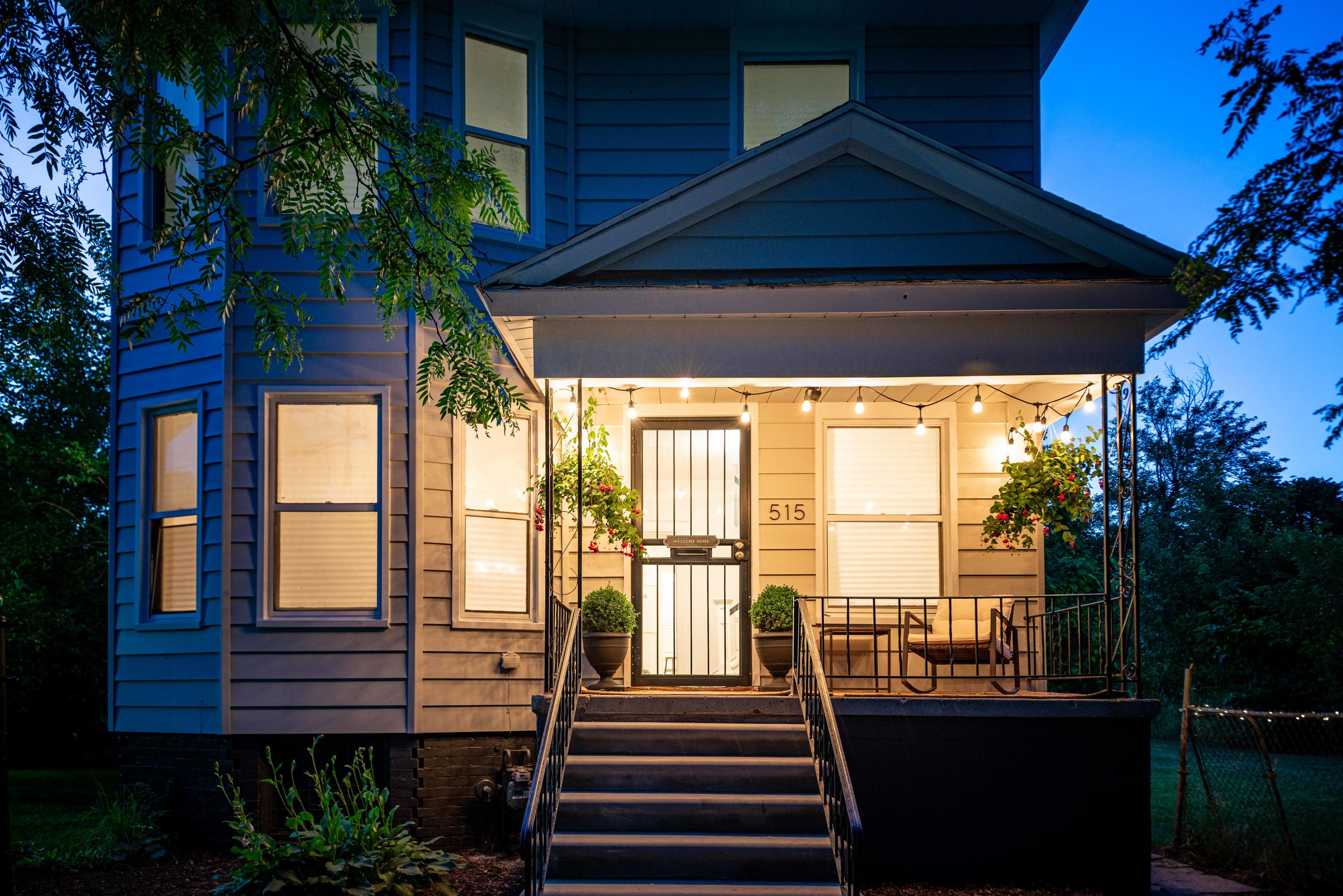 A home with white vinyl siding at dusk. The front porch is lit with strung Edison bulbs.