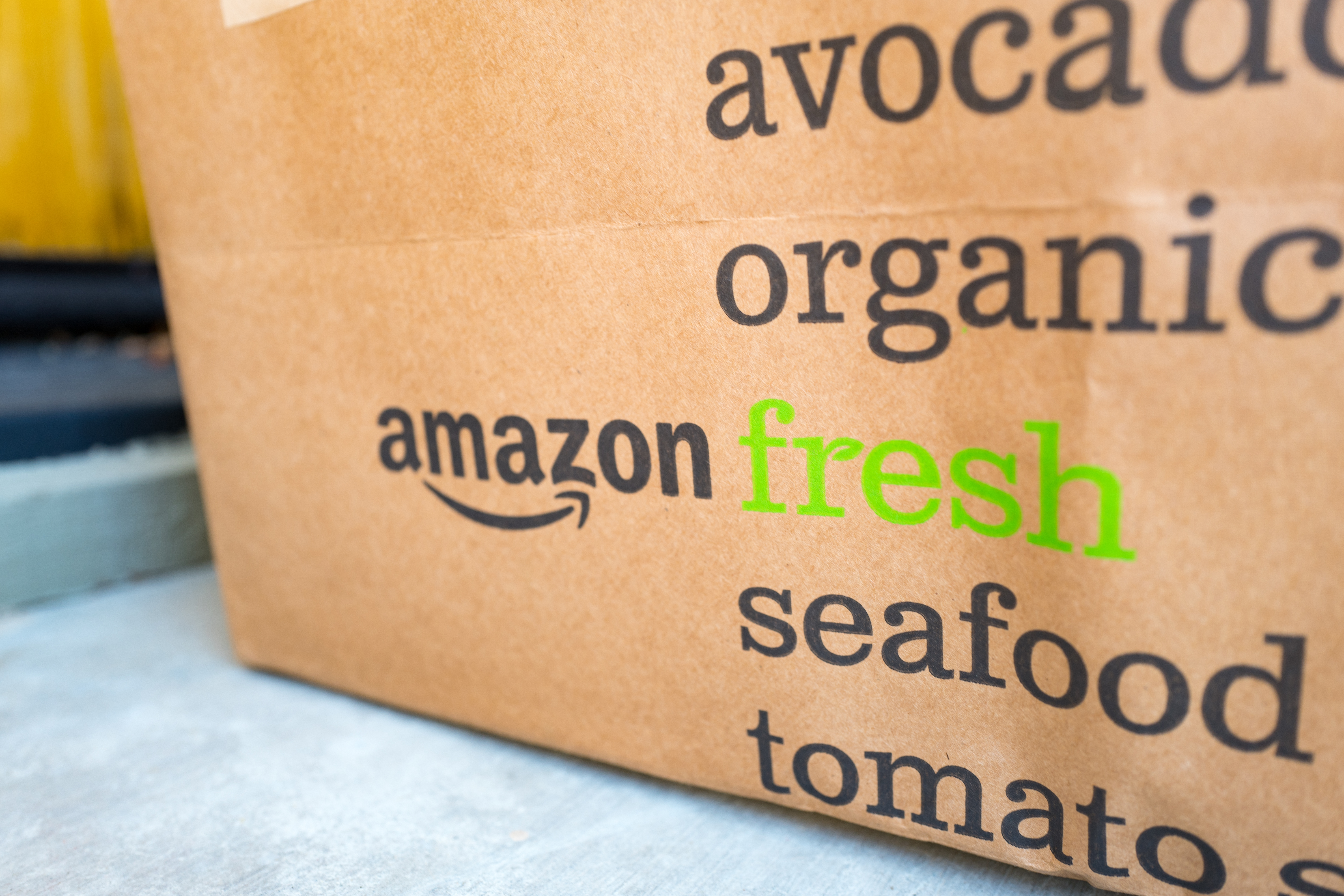 Brown paper tote for Amazon Fresh grocery delivery service, with Amazon logo and text listing groceries which may be ordered using the service