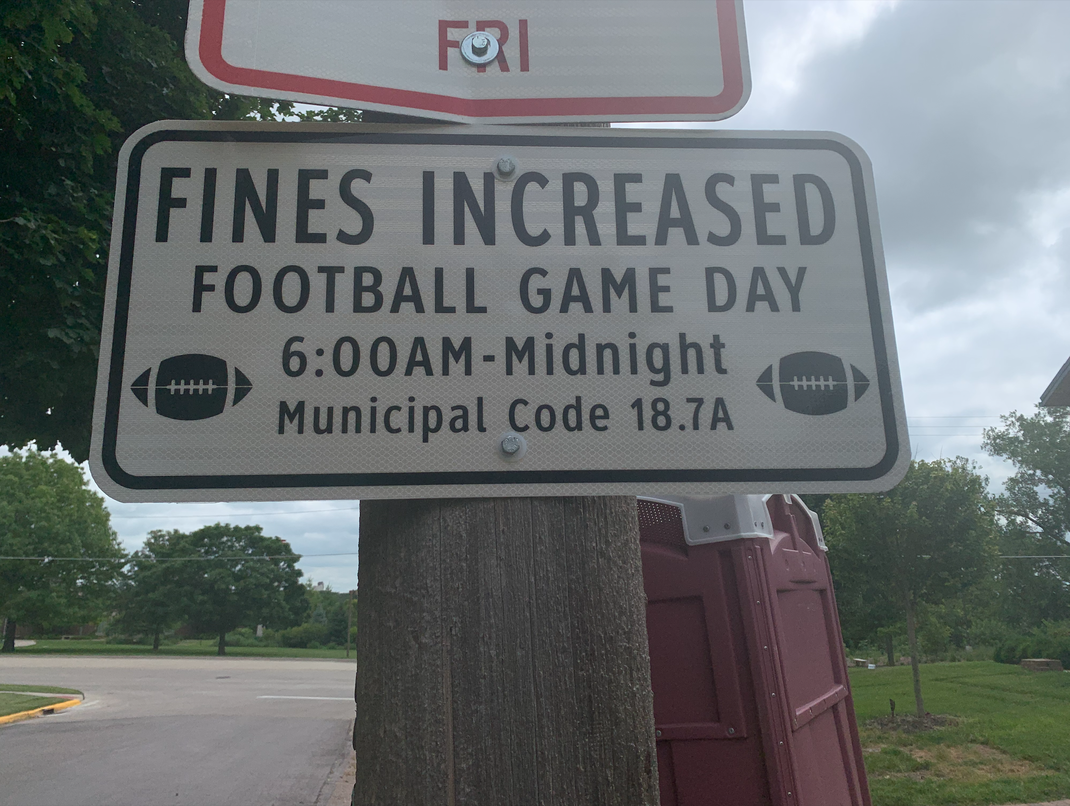 """A traffic sign (white rectangle, black text) that reads """"Fines Increased. Football Game Day. 6:00AM-Midnight. Municipal Code 18.7A"""""""