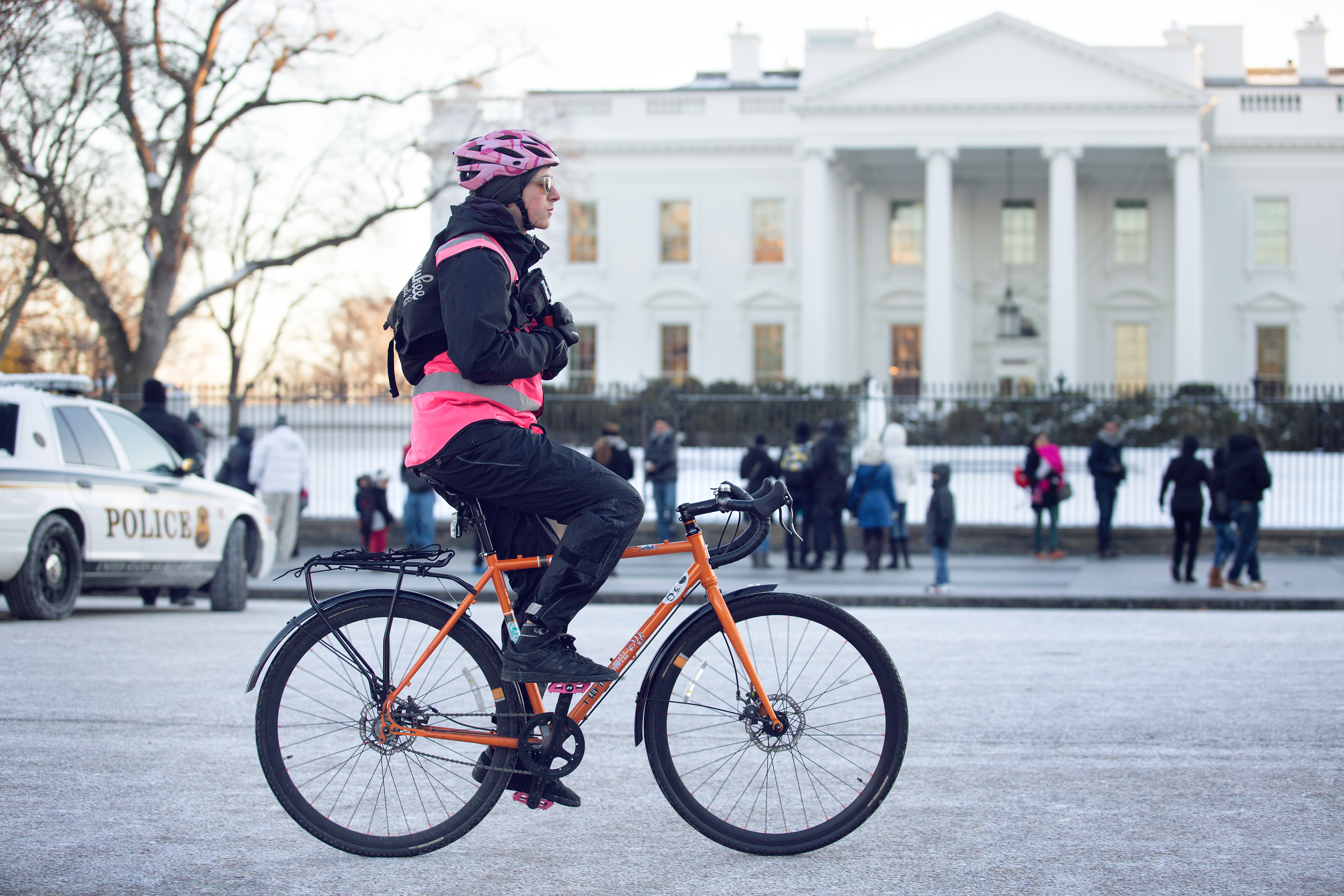 A Postmates bike messenger rides on Pennsylvania Avenue in front of the White House.