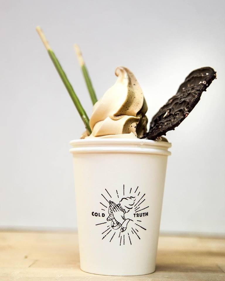 a white cup with a chocolate vanilla swirl of soft serve. It has two green matcha flavored Pocky sticks poking out of the top as well as a chocolate covered potato chip