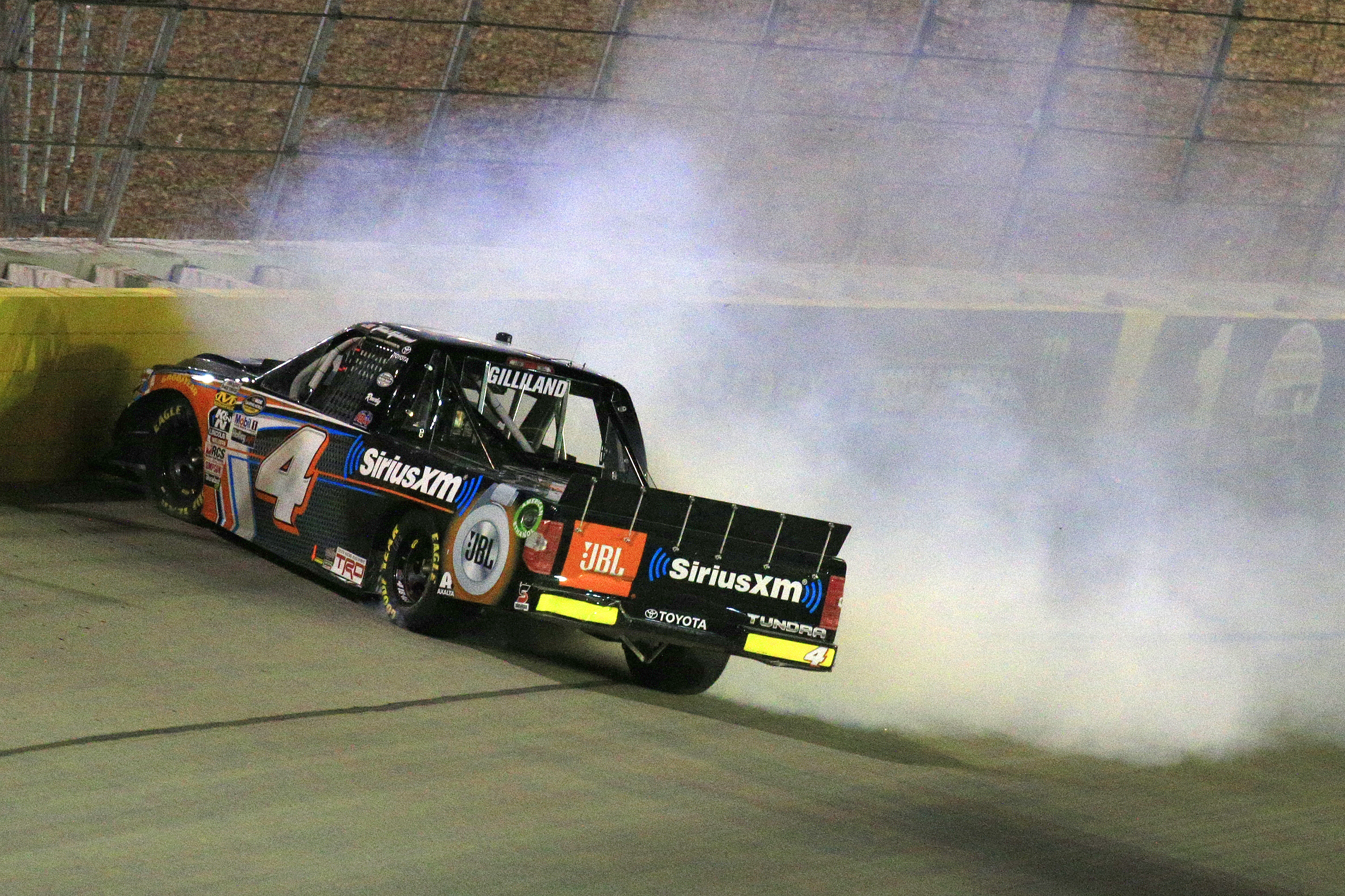 A mini pickup truck with smoke pouring out of its hood crashed into a wall on a race track.