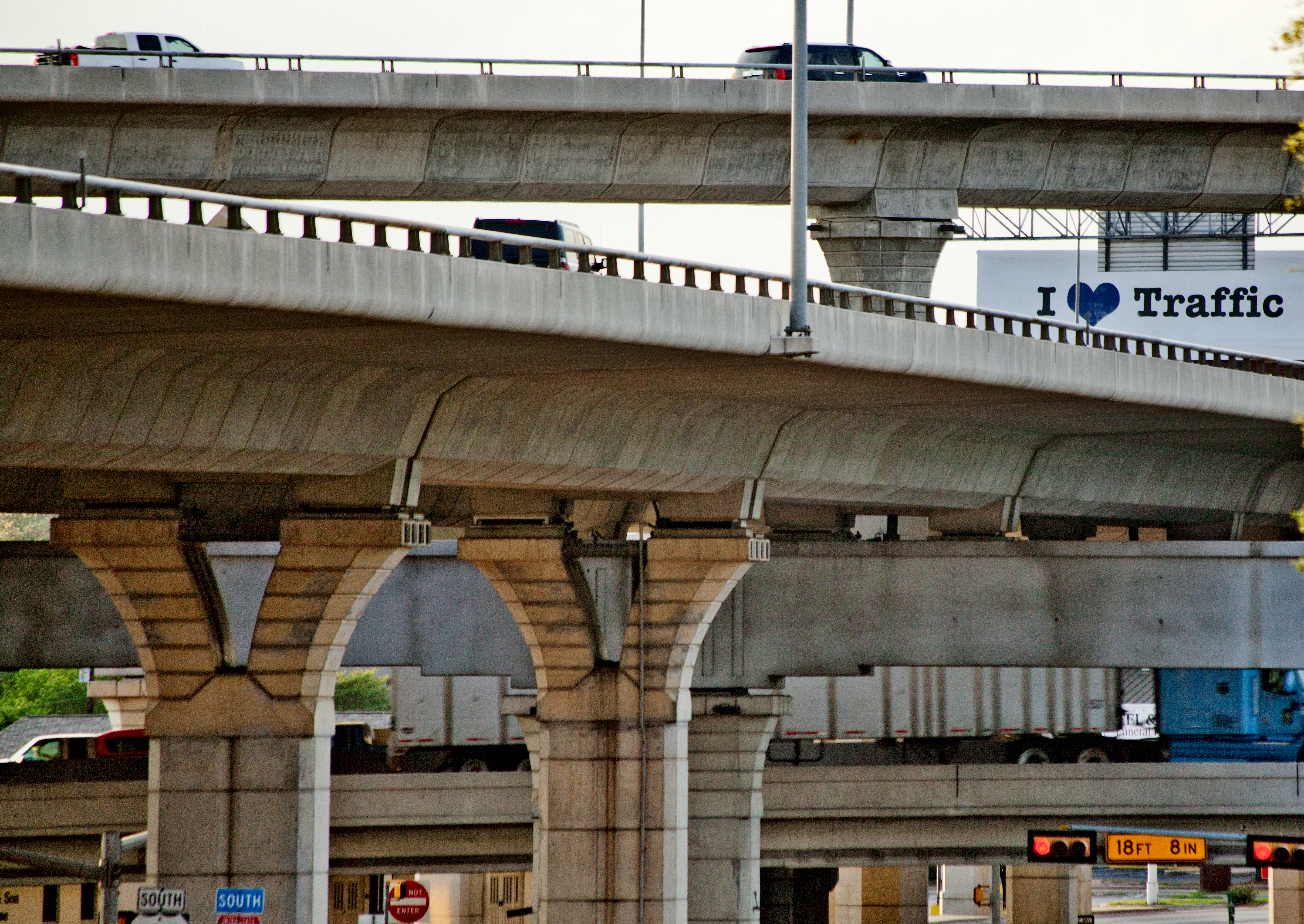 """A billboard with the text """" I love Traffic"""" is seen through the multistacked interchange between Interstate 35 and US-183 in North Austin."""
