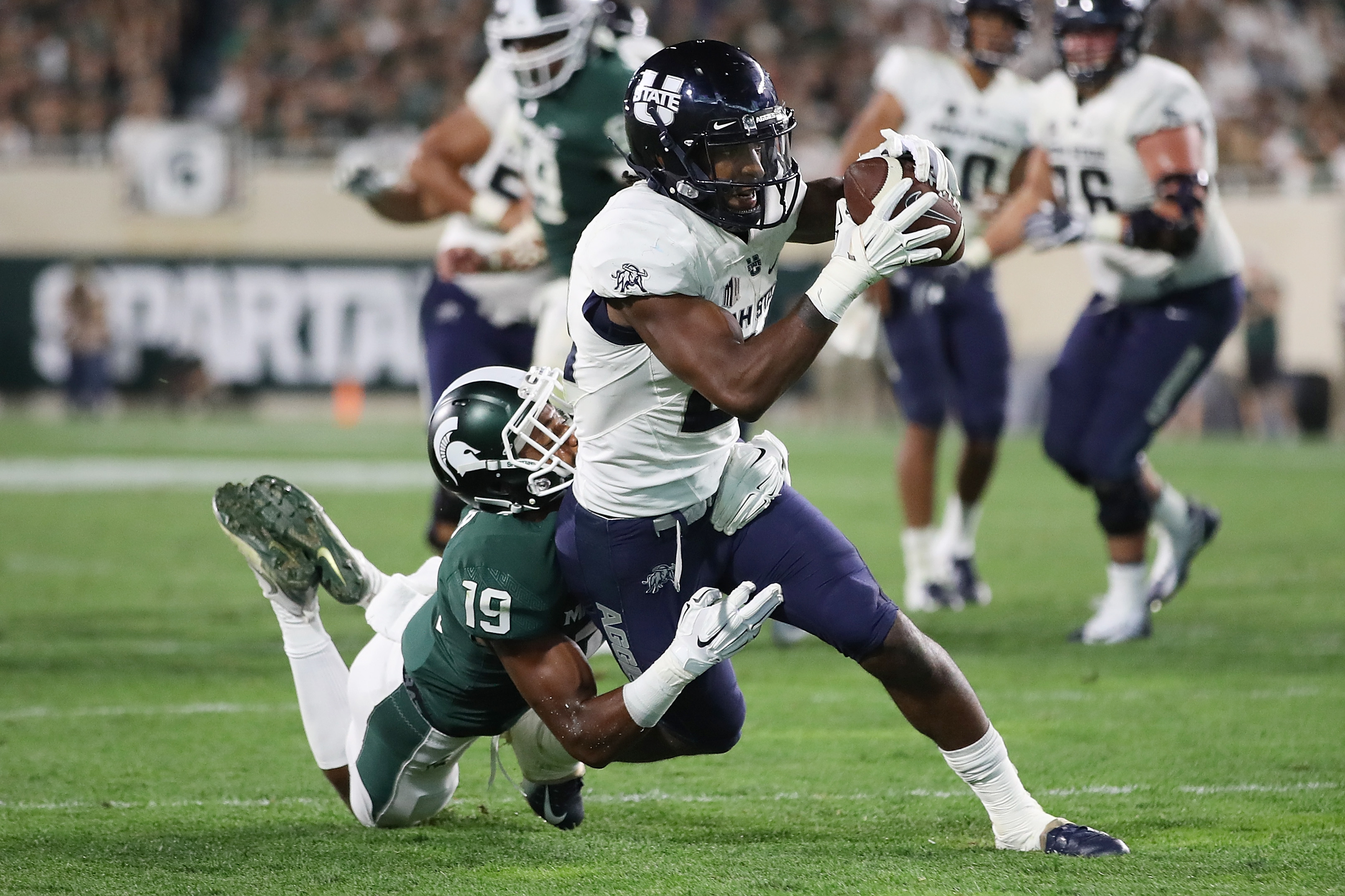 Utah State Aggies WR Jalen Greene tries to escape a tackle from Michigan State Spartans CB Josh Butler, Aug. 31, 2018.