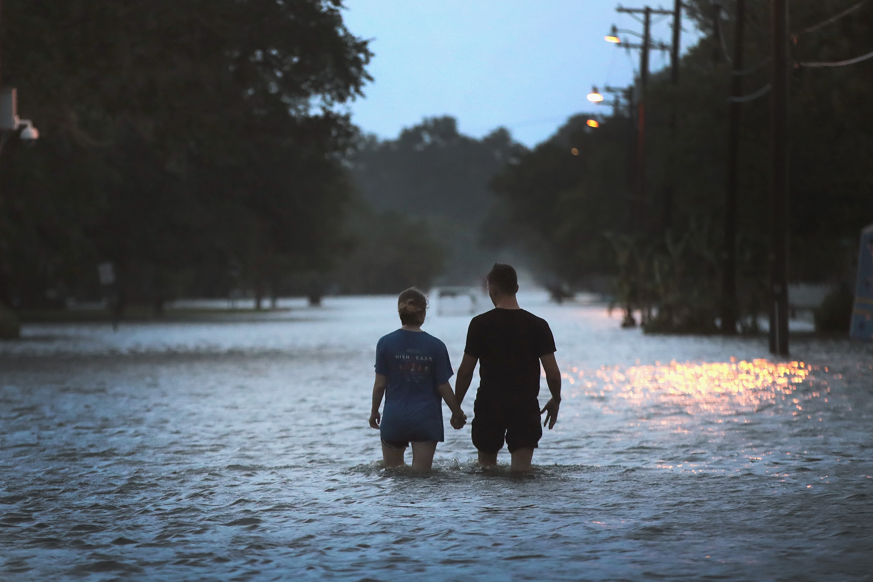 A couple walks through a flooded street in Mandeville, Louisiana.