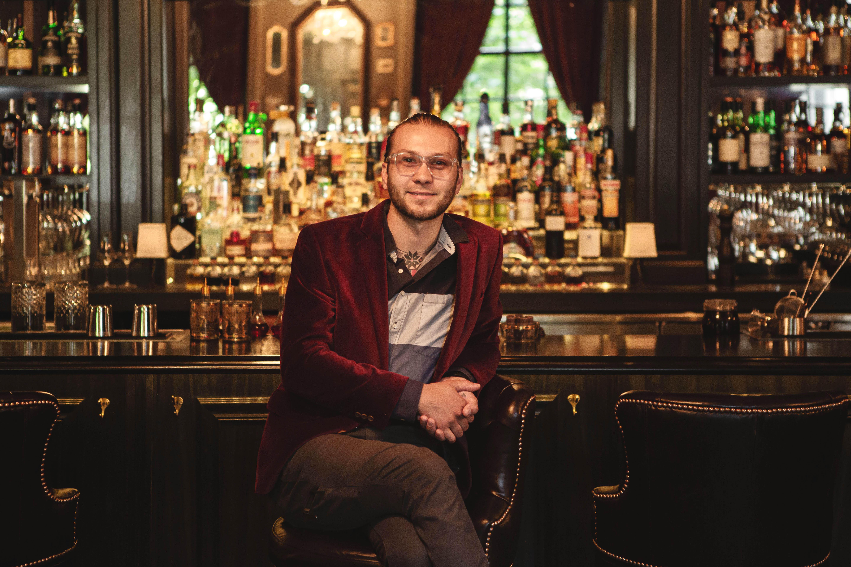 Keith Mrotek smiles at the camera, seated at the dark back bar at PS Steak