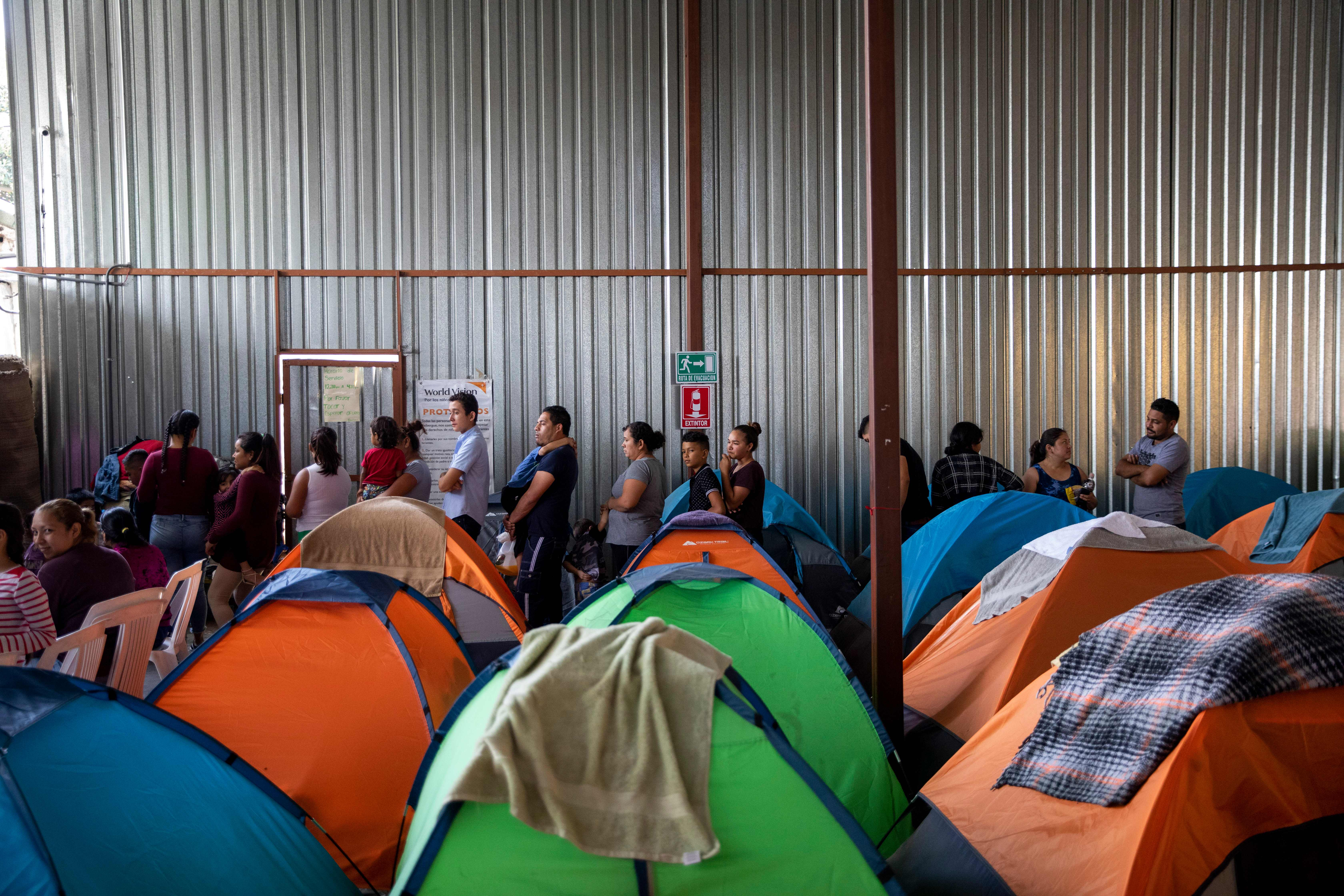 Asylum seekers wait in line behind a roomful of tents.