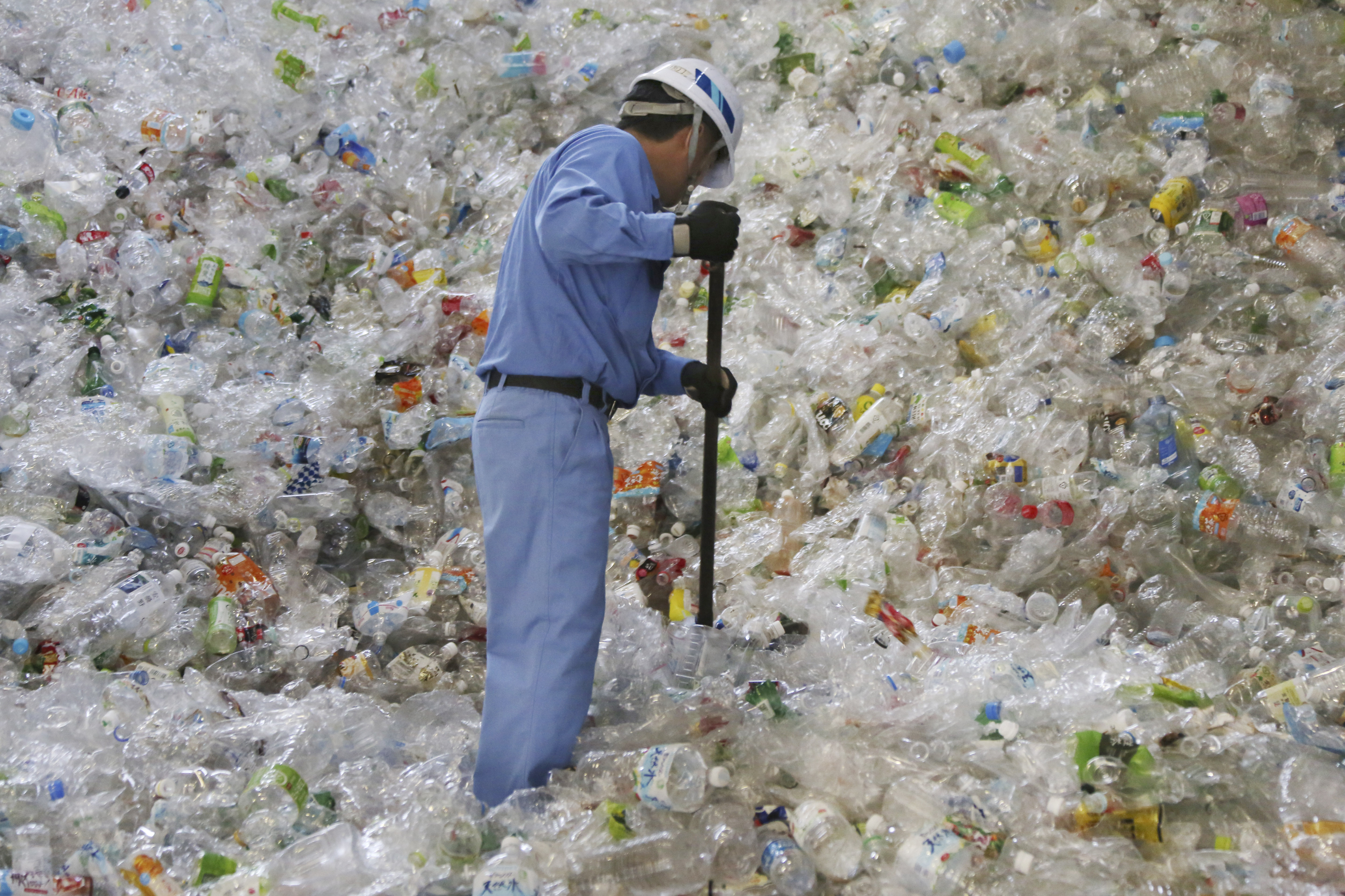 A worker at a Japanese recycling plant sorts out plastic bottles.