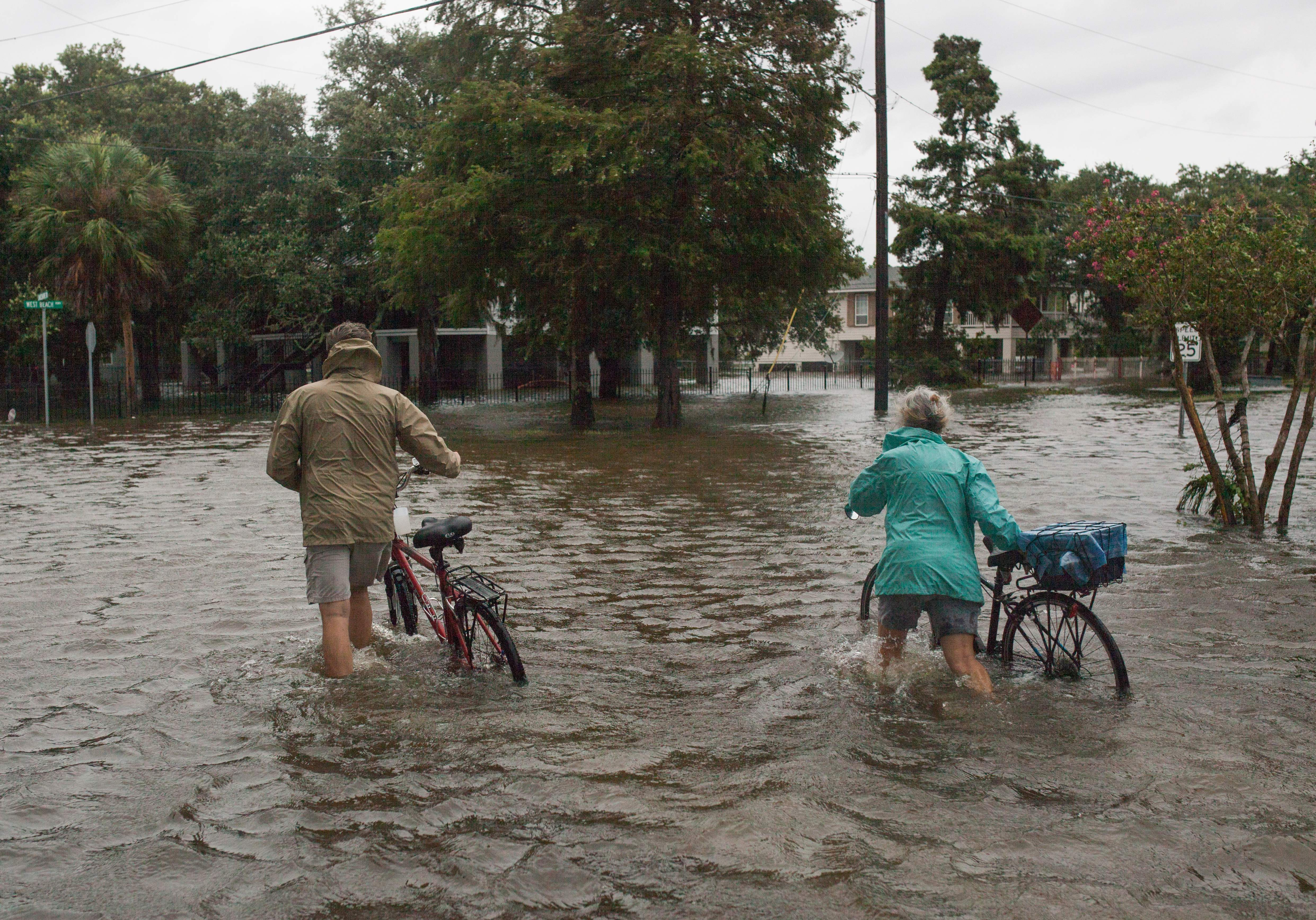 A couple walks their bikes through a flooded street after Tropical Storm Barry came ashore in Mandeville, Louisiana on July 14, 2019.