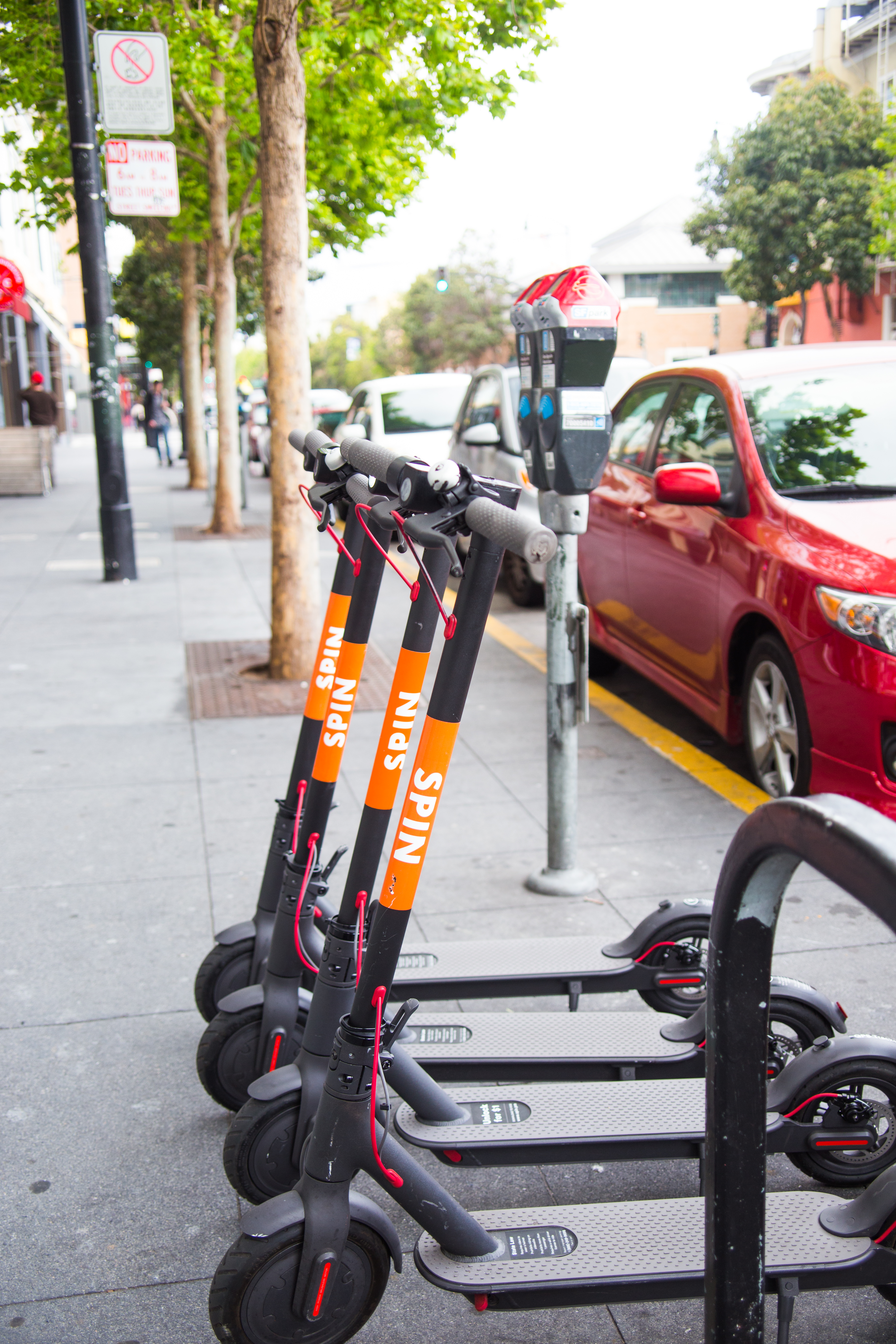 Spin scooters (with orange labels) parked on sidewalk in front of parking meter and red car
