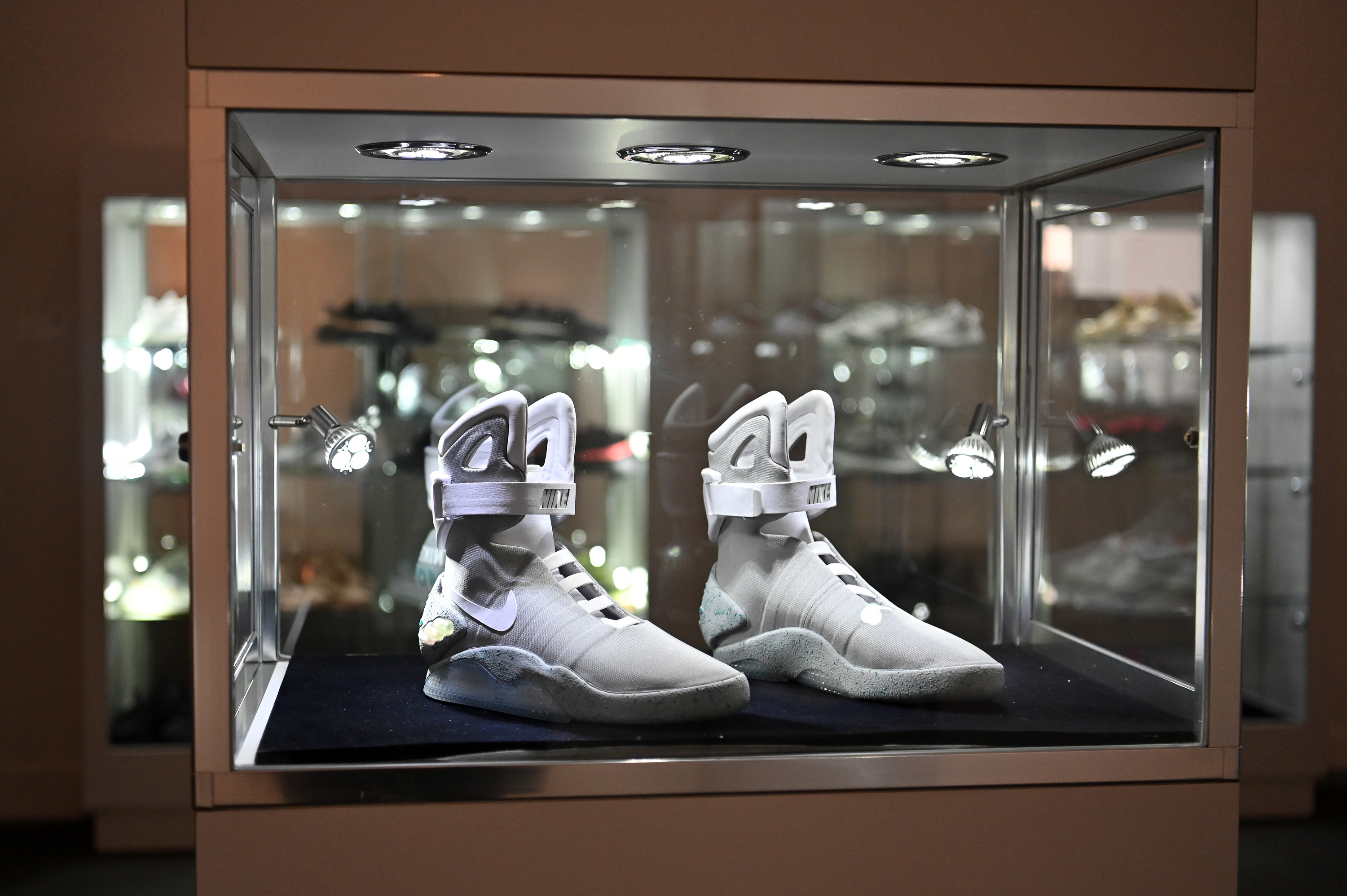 A pair of sneakers inside a lighted glass case.
