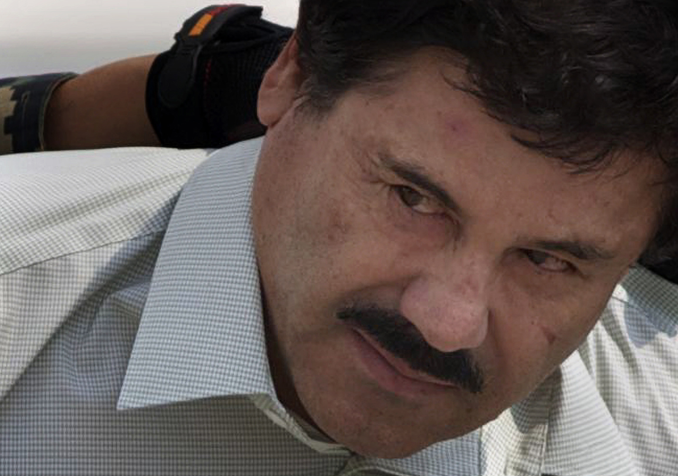 """Joaquin """"El Chapo"""" Guzman Loera as he was escorted to a helicopter in handcuffs by Mexican navy marines at a navy hanger in Mexico City on Feb. 22, 2014."""