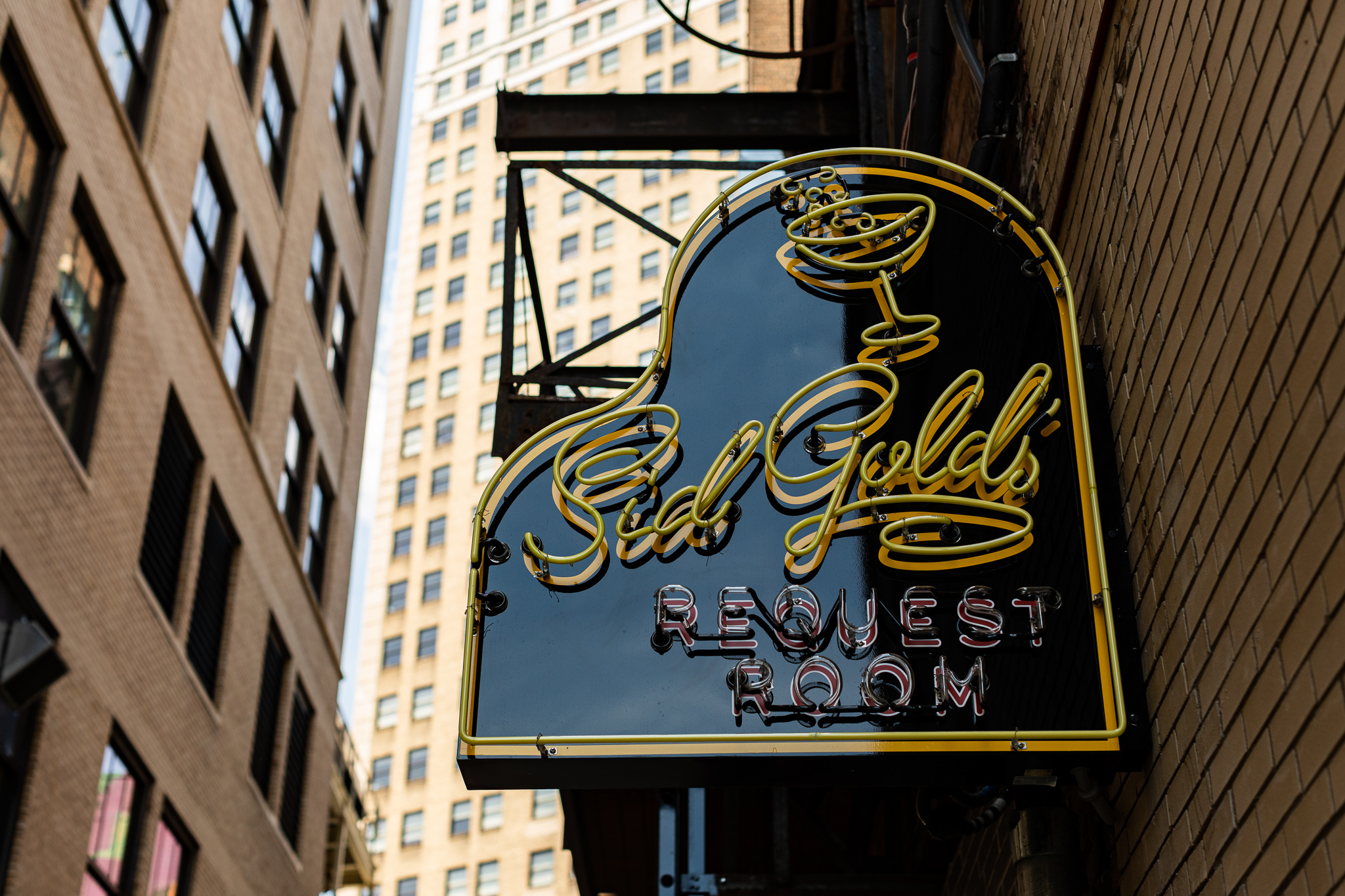 The piano-shaped sign at Sid Gold's when it's still light out. It's built with neon yellow curvy writing with a cocktail coup glass