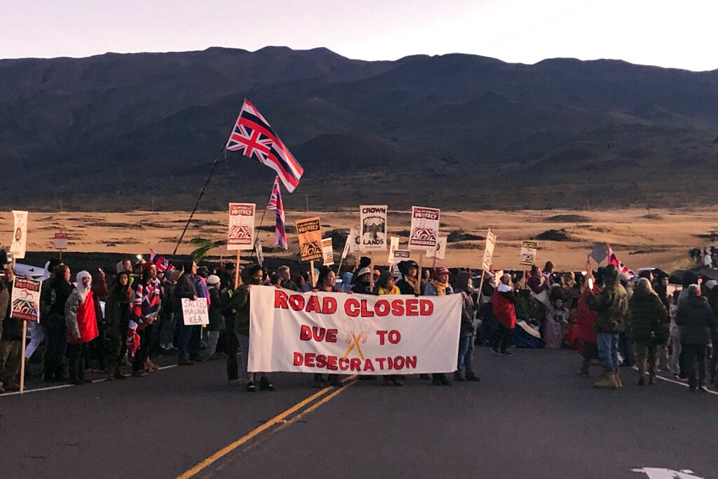 Demonstrators are gather to block a road at the base of Hawaii's tallest mountain, Monday, July 15, 2019, in Mauna Kea, Hawaii, to protest the construction of a giant telescope on land that some Native Hawaiians consider sacred.
