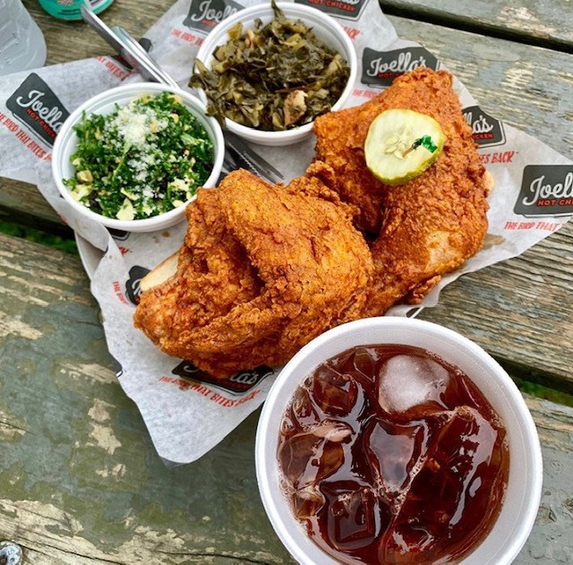 A hot chicken thigh and leg and hot chicken breast and wing with collards and kale salad and a black cherry soda