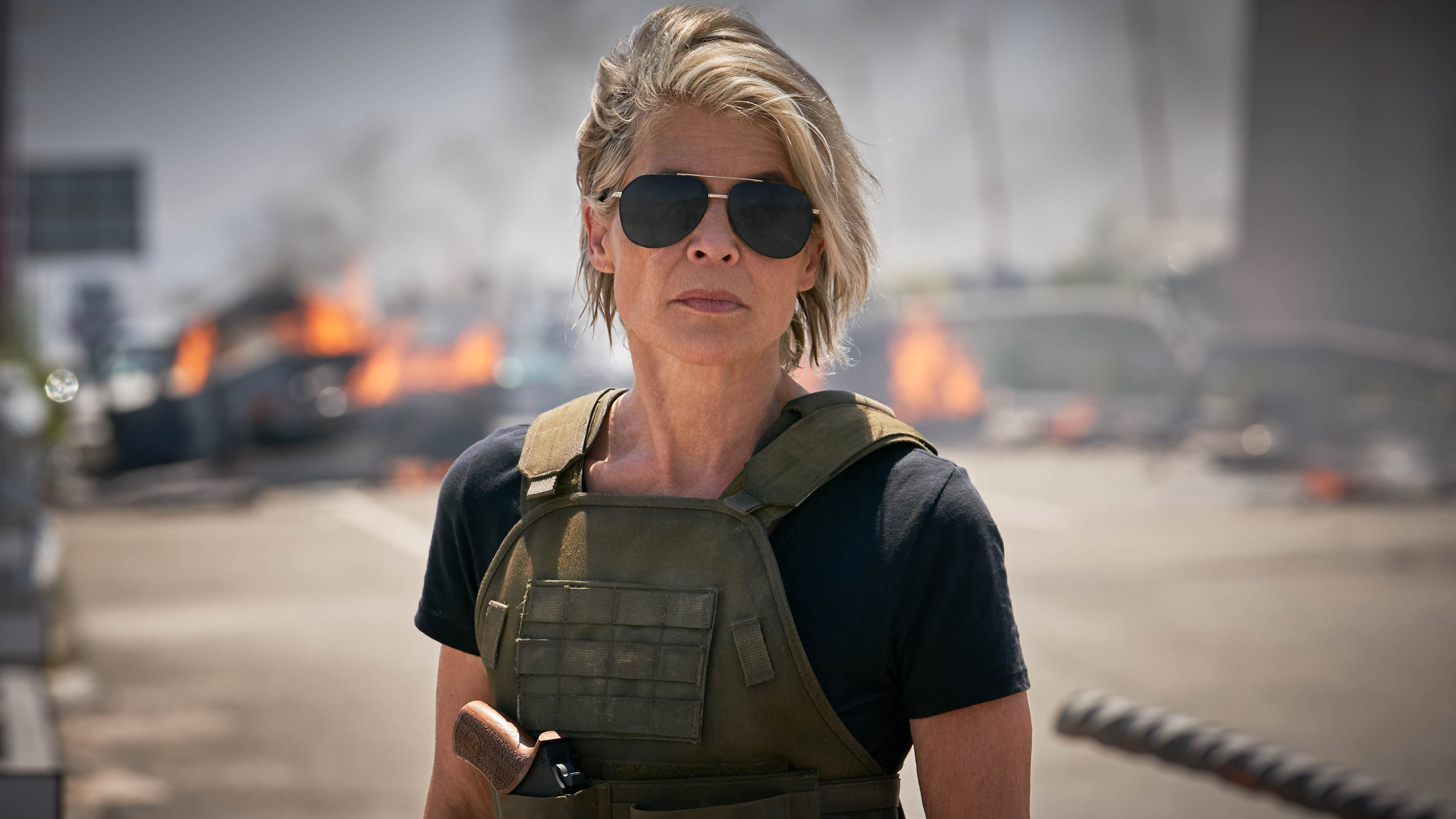 Linda Hamilton, wearing a combat vest and aviator classes, looking non-plussed.