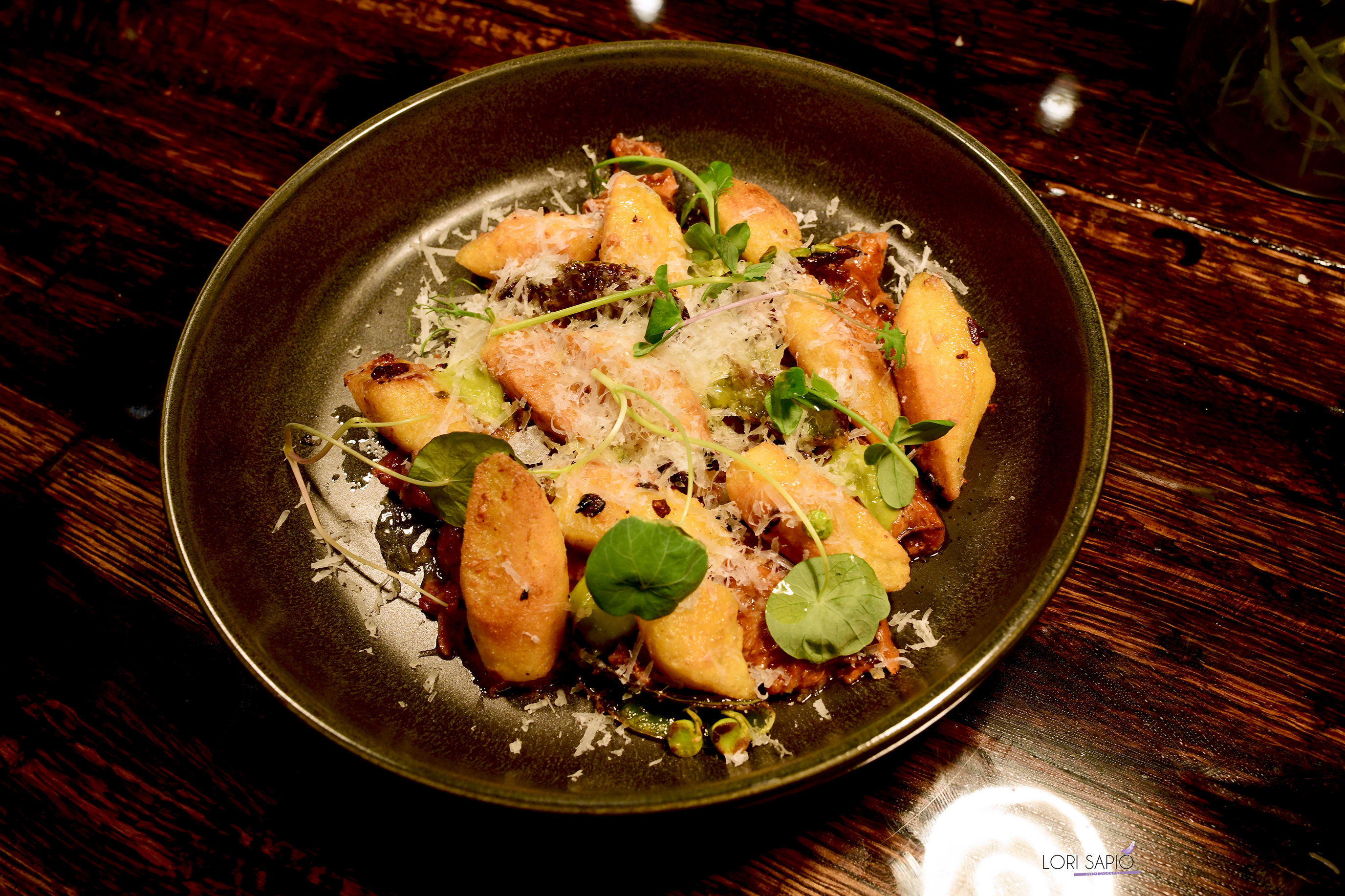 A small pile of orange-colored yucca dumplings sit on a charcoal-colored plate and are topped with shredded cheese and herb leafs.