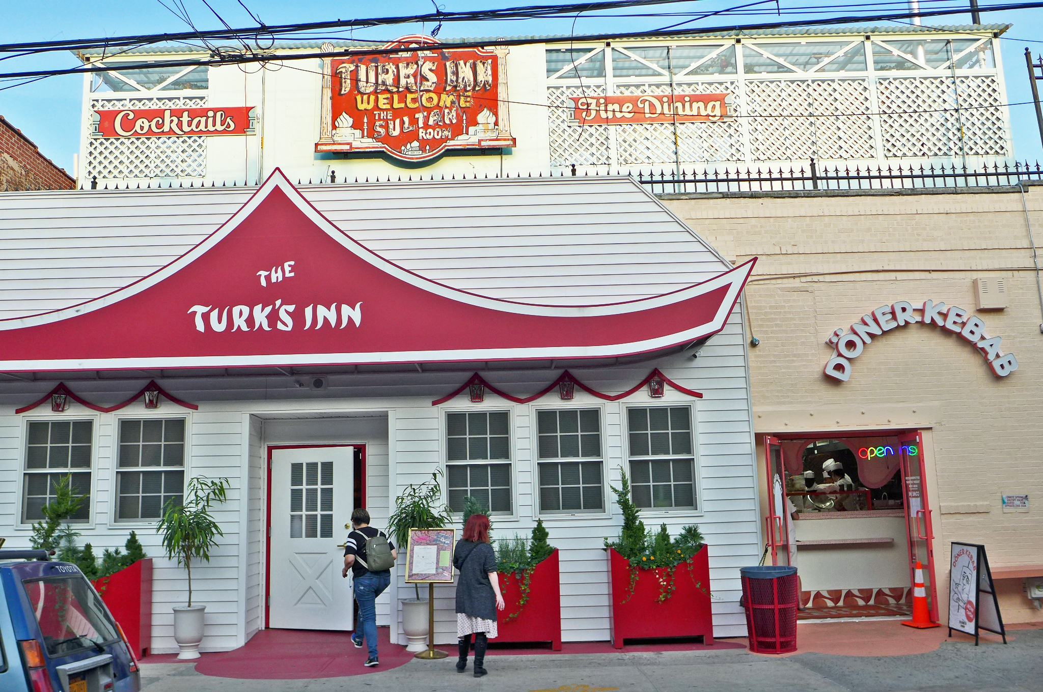 "The Turk's Inn restaurant is inside a building that looks like a white house, with a red awning and a neon ""Turk's Inn"" sign up top."
