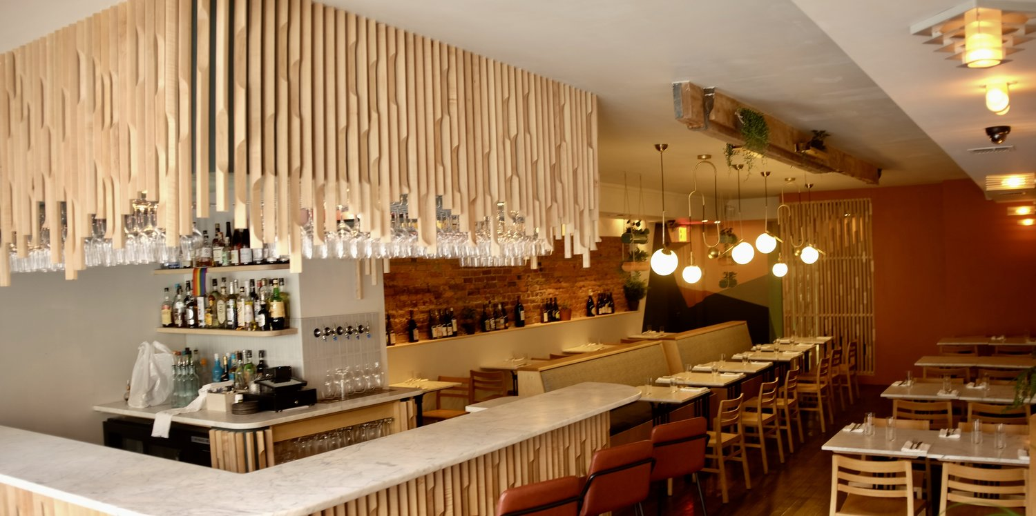 L'Accolade's blonde dining room, with an off-white counter and reddish brown stools